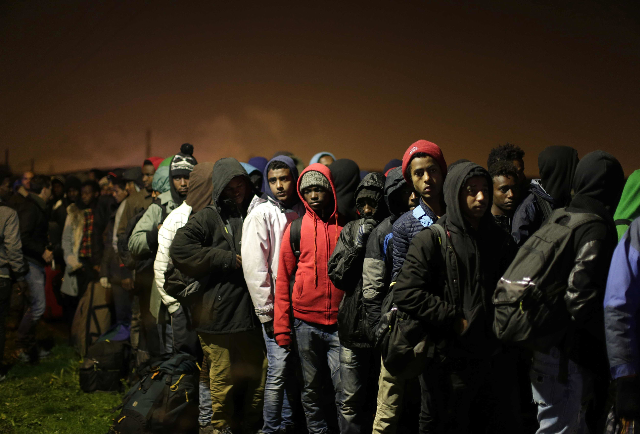 Migrants line up to register at a processing center in the makeshift migrant camp known as  the Jungle,  near Calais, northern France, on Oct. 24, 2016.