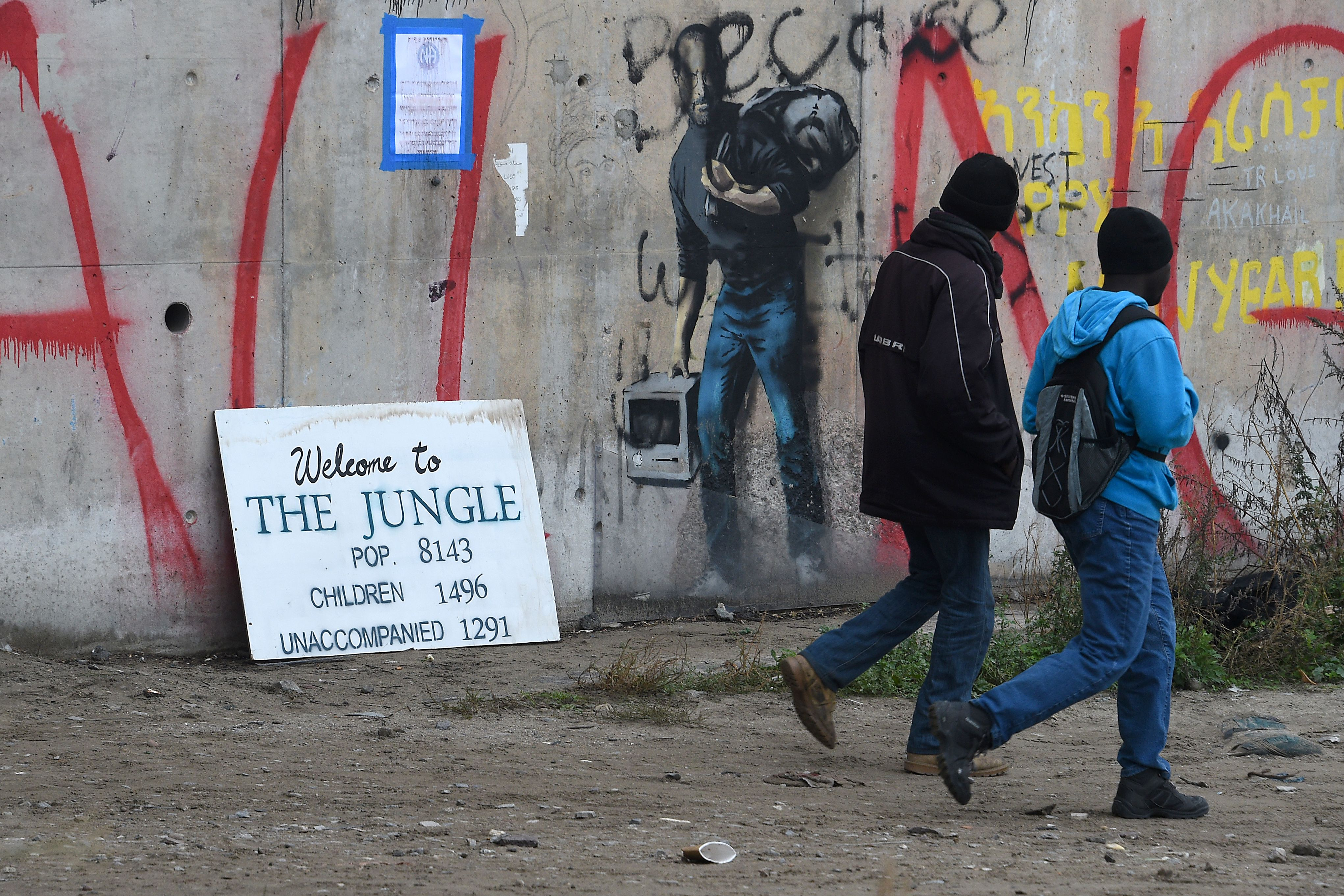 Migrants walk past a graffiti by street artist Banksy representing Apple founder Steve Jobs as a migrant during the full evacuation of the Calais  Jungle  camp, in Calais, northern France, on October 24, 2016.