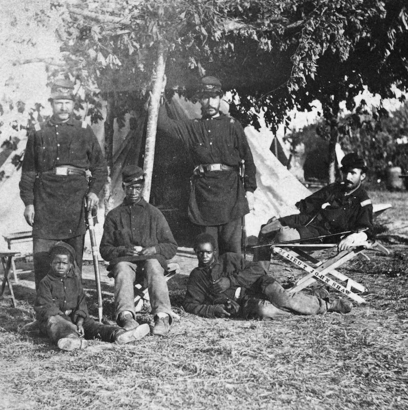 Capt. B.S. Brown (left); Lt. John P. Shaw, Co. F 2nd Regt. Rhode Island Volunteer Infantry (center); and Lt. Fry (right) with African-American men and boy contrabands at a Civil War camp in 1863.