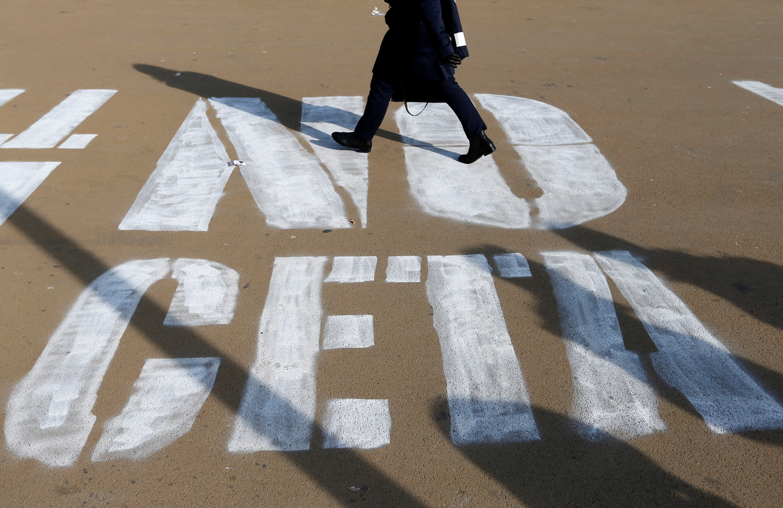 A woman walks on a graffiti reading  NO CETA , referring to the Comprehensive Economic and Trade Agreement, in Brussels on October 13, 2016.