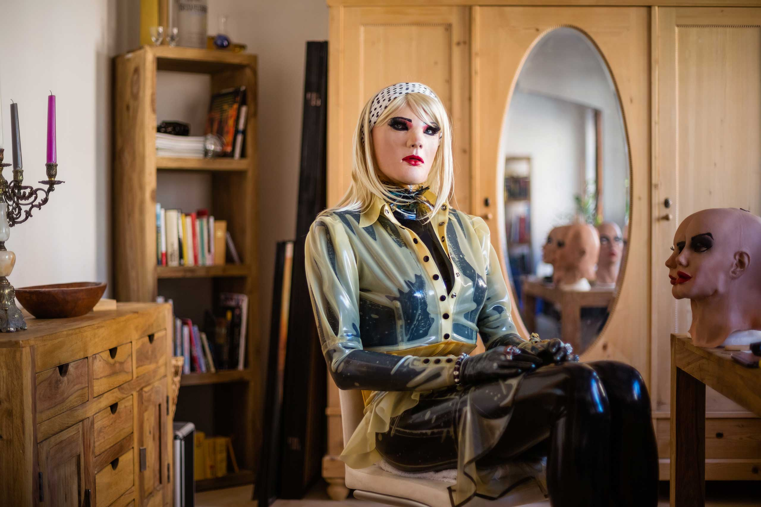 Portrait of female masker Christian alias 'Chrissie Seams', double the age of his alter ego, in his living room. Female masking presents an outlet for him, as a heterosexual and cisgender male, to live out his female side and latex fetish. On his right stand a variety of masks that he uses for experimenting with airbrushing and other alteration techniques in order to individualise the look of his alter ego.                                                                Since my childhood I have been fascinated by latex, which very soon merged with my aspirations to look as sexy as a woman. I remember the first time I had the wish to slip into a woman's skin was at the age of 14 when I saw a model wearing sexy lingerie in a Penthouse magazine. I imagined slipping into her skin, like slipping into a surface made from latex.                               I love the feeling of being encapsulated and the sensitization from head to toe when wearing latex. At the same time I endeavor aesthetics. Visually, I only like latex on women, hence I don't gain anything from my fetish if not dressed as a woman myself. Many times I wondered if there was a Chrissie if it wasn't for my passion for latex.                                Augsburg, Germany, Aug. 5, 2015.