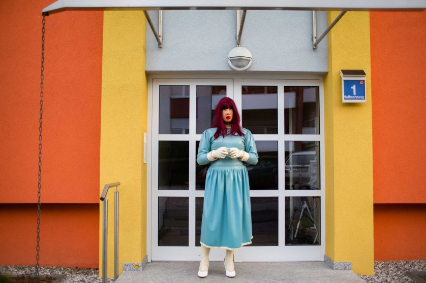 """ELZE, GERMANY - AUGUST 20, 2015: Female masker and transsexual woman Katrina, 46, in front of her home August 20, 2015 in Elze, Germany. """"What fascinates me is the immunity. The 'being-me'. You are encapsulated. Like in a cocoon. They don't see you. They don't see your mimic, if you laugh or if you cry. The unknown behind it. This anonymity.""""- Female Masker Katrina, 46, transsexual woman""""In latex I am courageous. I like the provocation when going out in public as a rubberdoll. You don't see latex on every street corner, in the eyes of most people you are perverted or abnormal. That makes me think 'I show you that there is something else'. """"- Female Masker Katrina, 46, transsexual woman"""