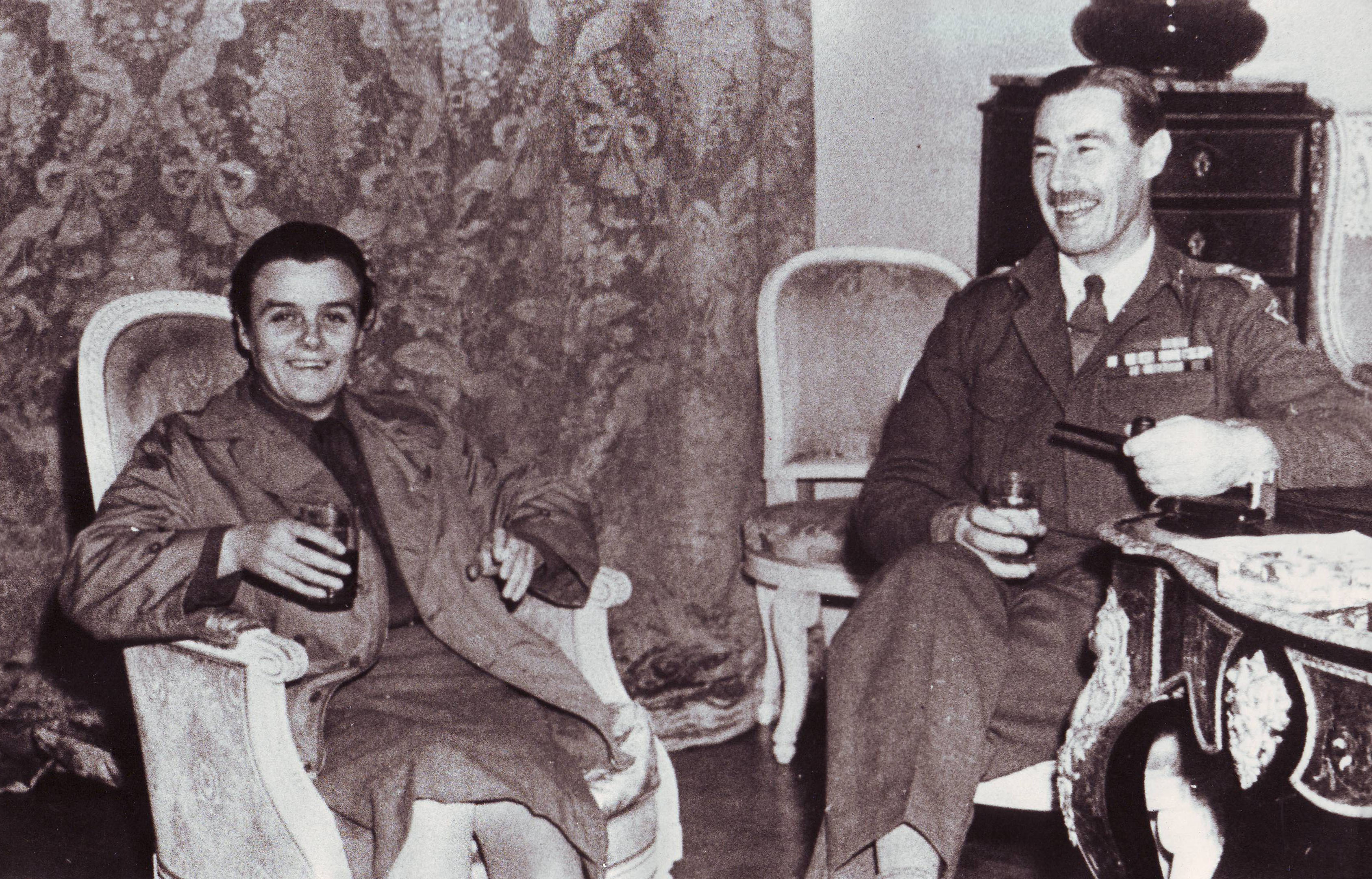 Clare Hollingworth with a military figure lounging in arm chair, likely towards the end of World War II.