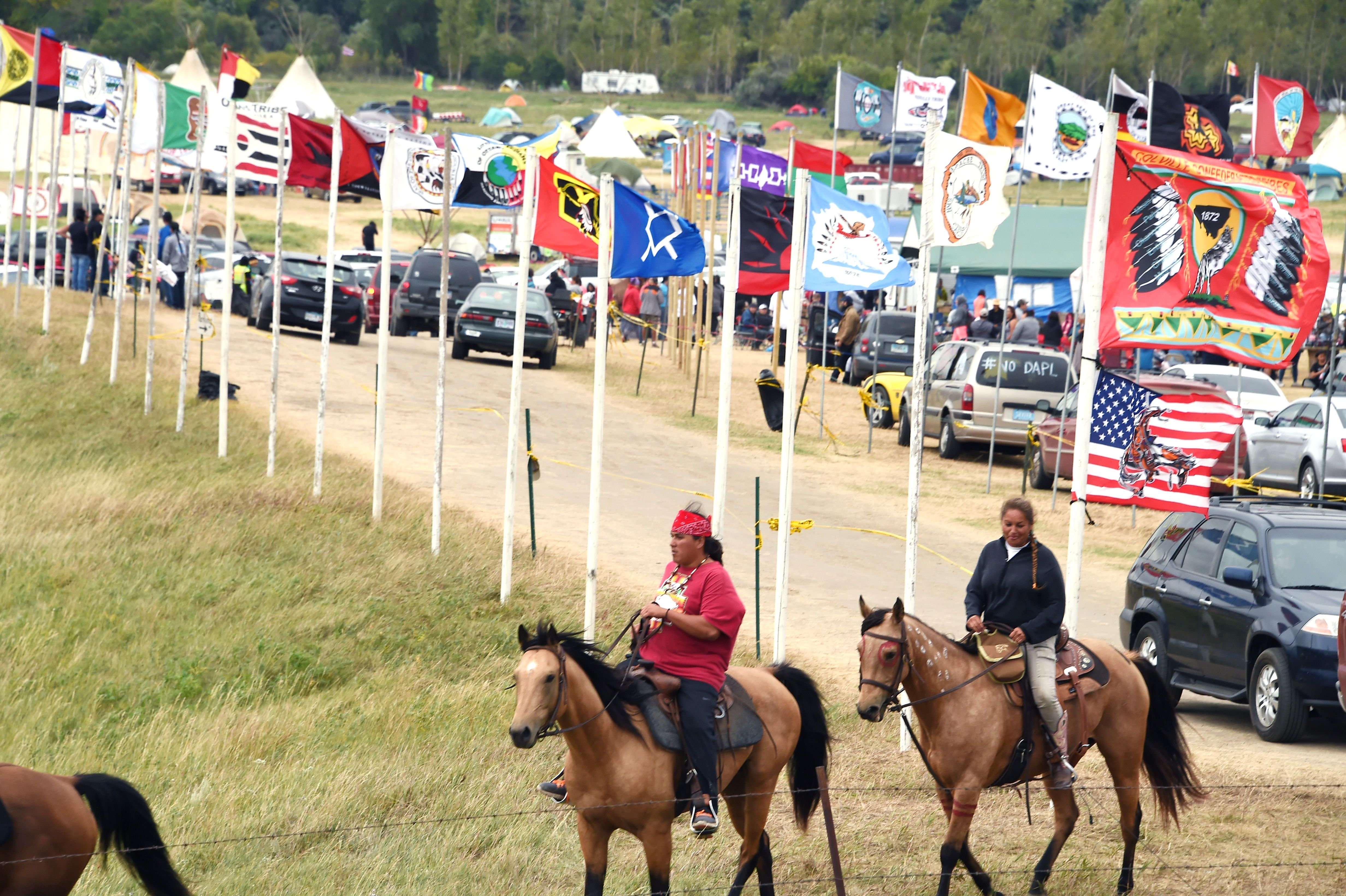 Flags of Native American tribes from across the US and Canada line the entrance to a protest encampment near Cannon Ball, North Dakota where members of the Standing Rock Sioux Tribe and their supporters have gather to voice their opposition to the Dakota Access Pipeline, Sept. 3, 2016.