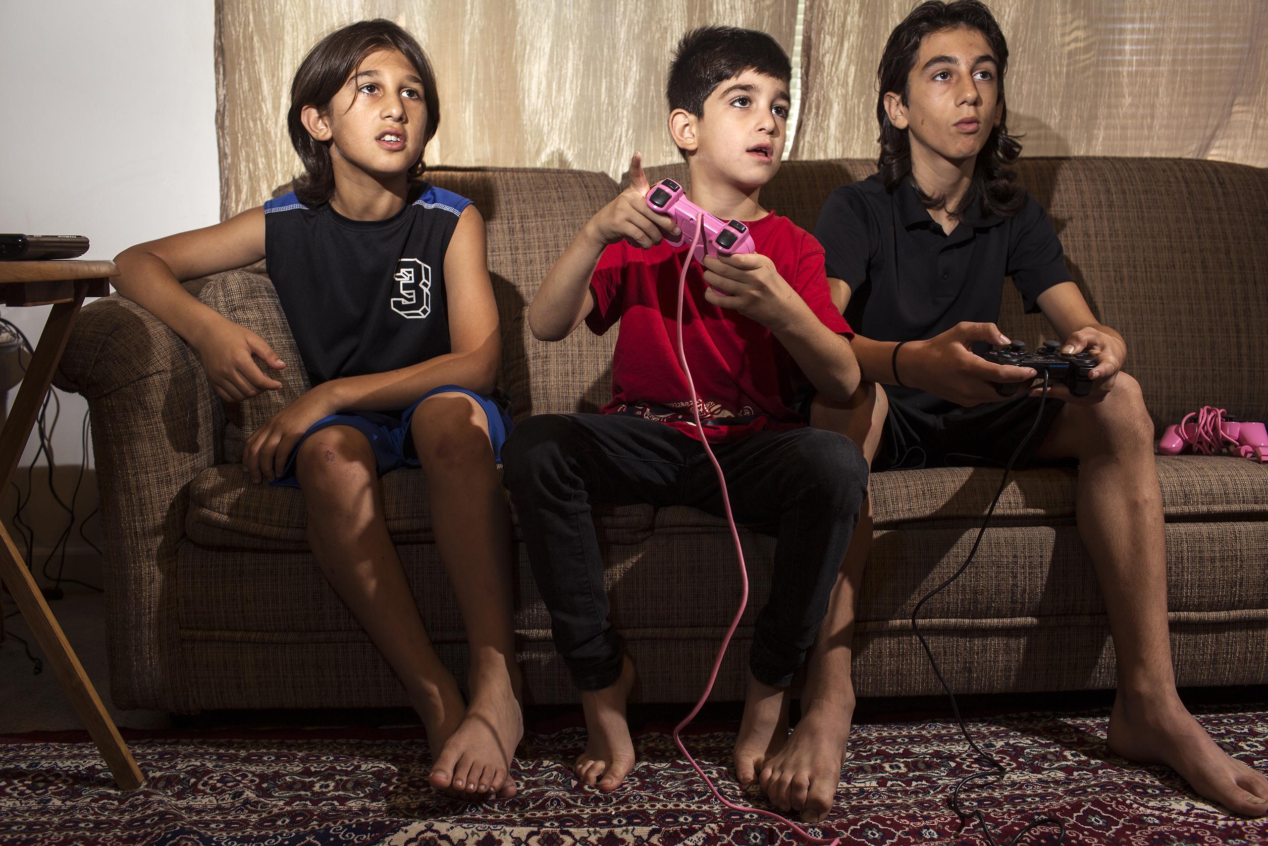 Haidar, Mutaz and Nazeer Tameem play video games at their apartment in Des Moines, Iowa.