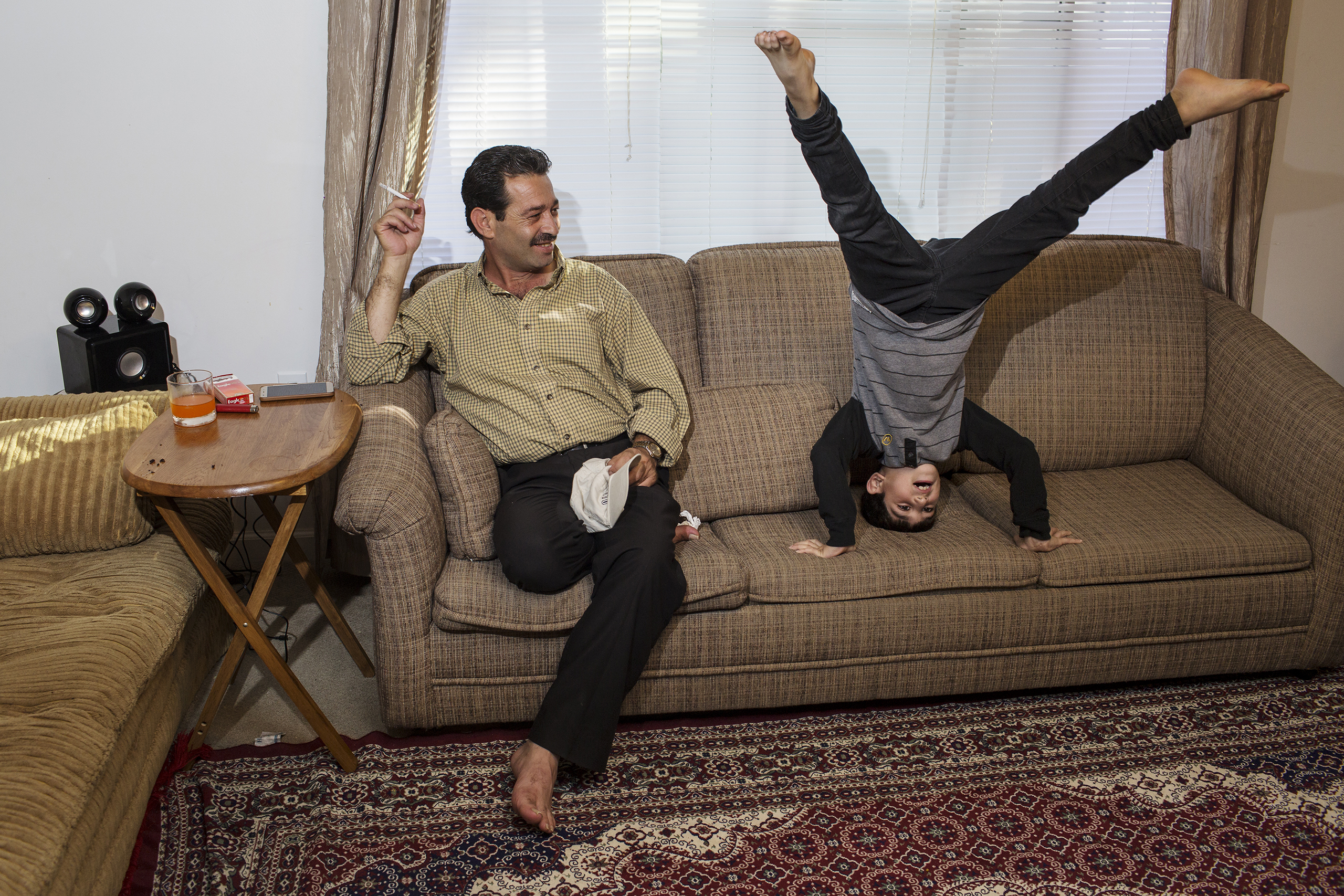 Mutaz Tameem, 6, plays inside the family's apartment in Des Moines, Iowa, while his father, Abdul Fattah, looks on.