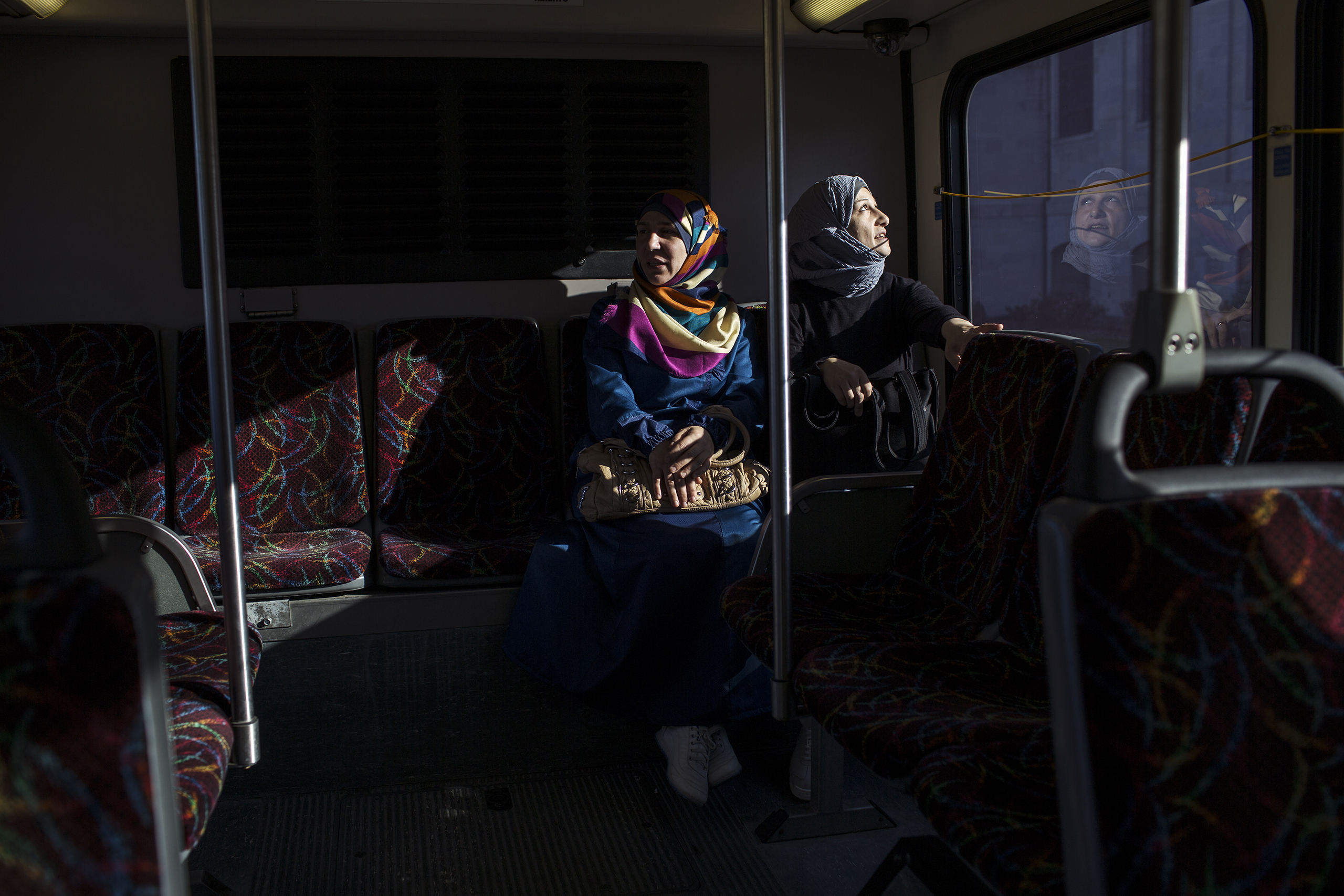 Ghazweh and her friend, Mumena El Ali, ride the bus while on their way to ESL class at the Des Moines Area Community College.