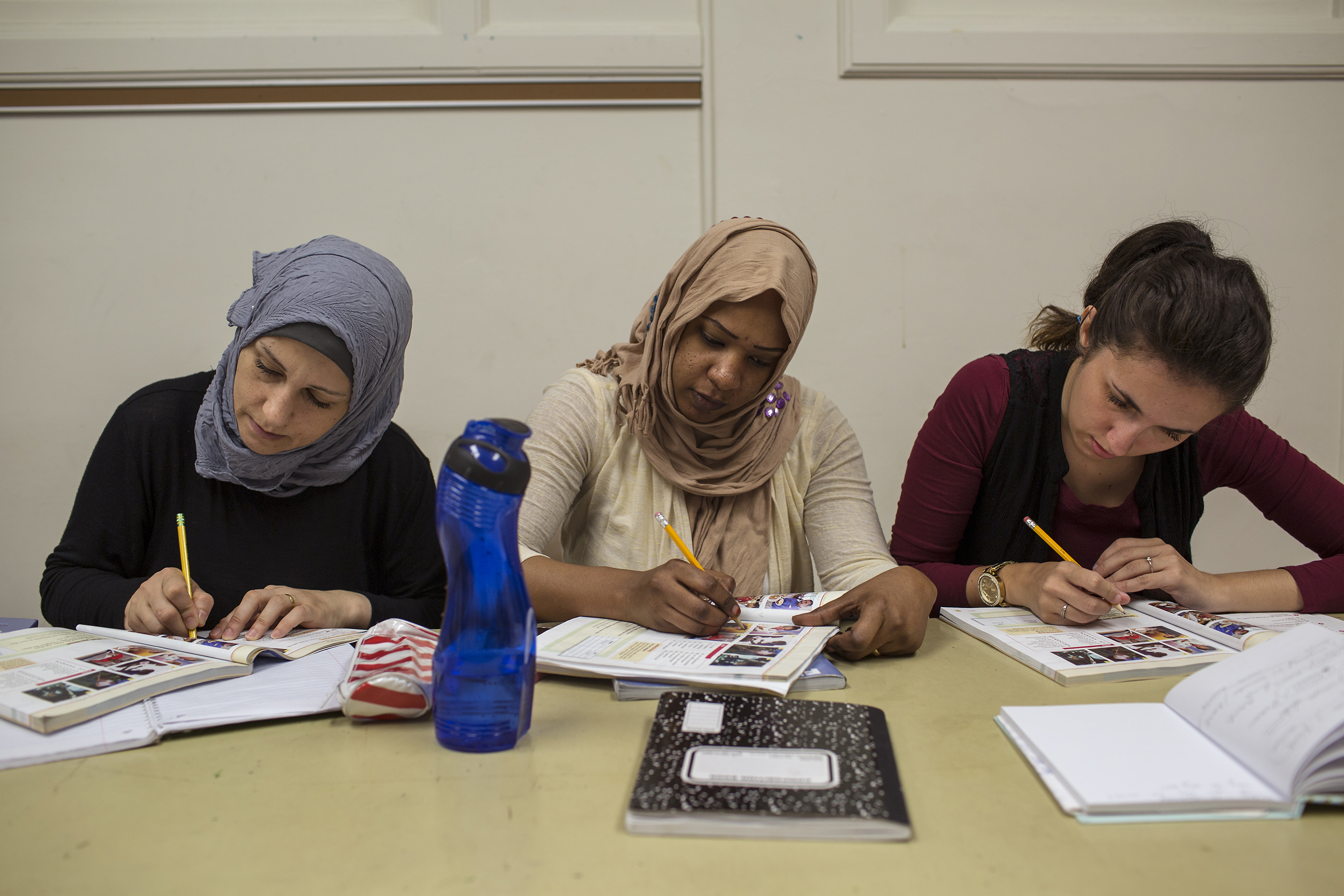 Ghazwa, Mrwah Shanpia and Arnela Omerovic write during their ESL class at the Des Moines Area Community College.