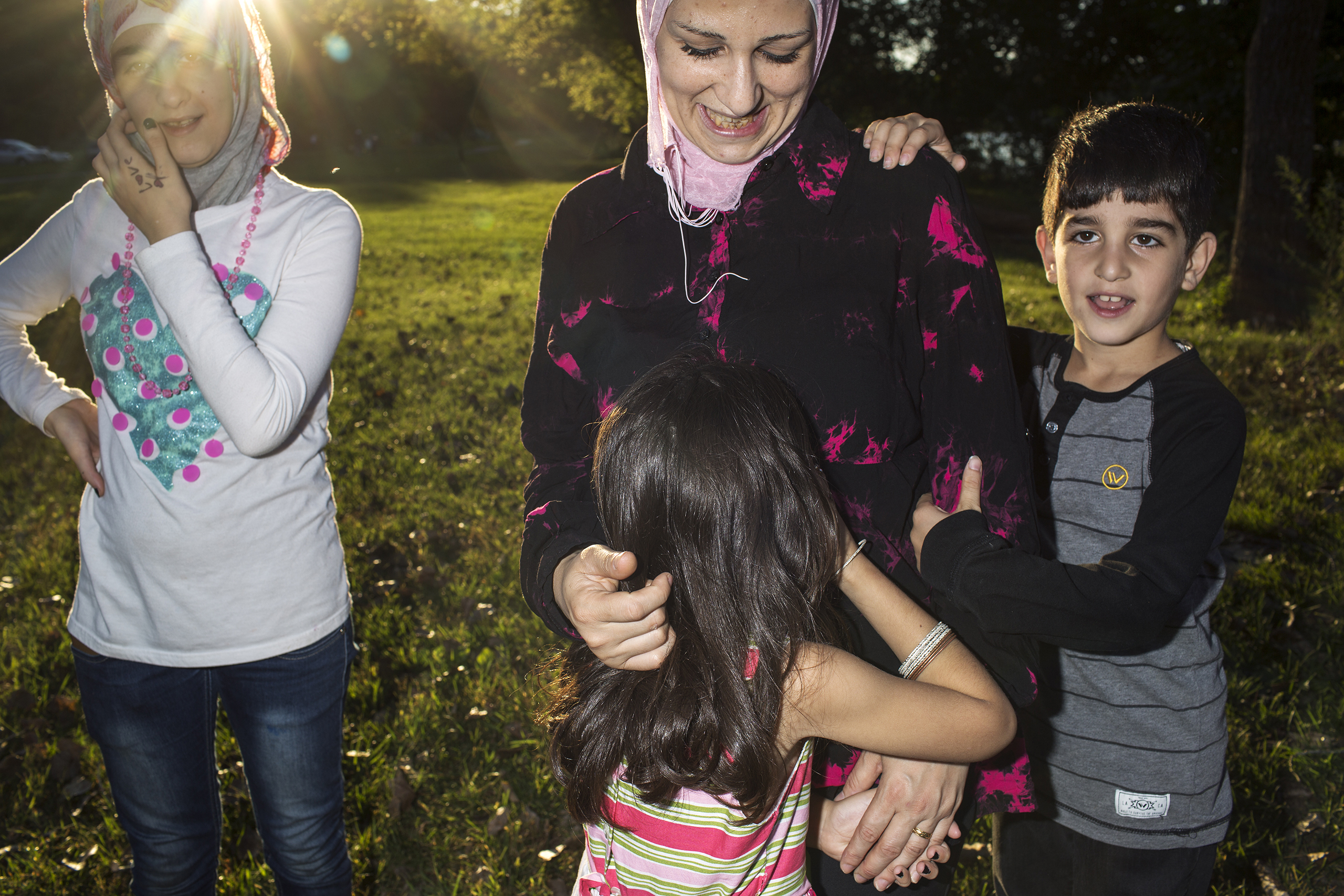 Ghazweh plays with her children Sedra, Hala and Mutaz at a park in Des Moines, Iowa.