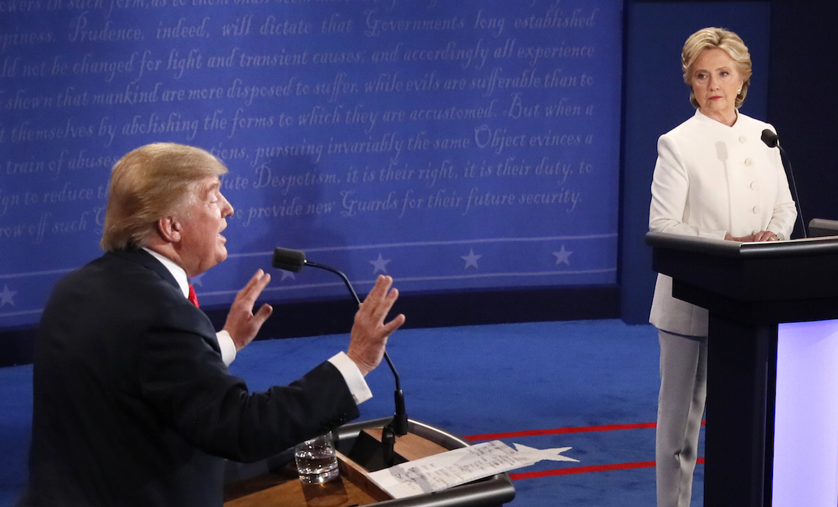 Republican nominee Donald Trump gestures as Democratic nominee Hillary Clinton looks on during the final presidential debate in Las Vegas on Oct. 19, 2016