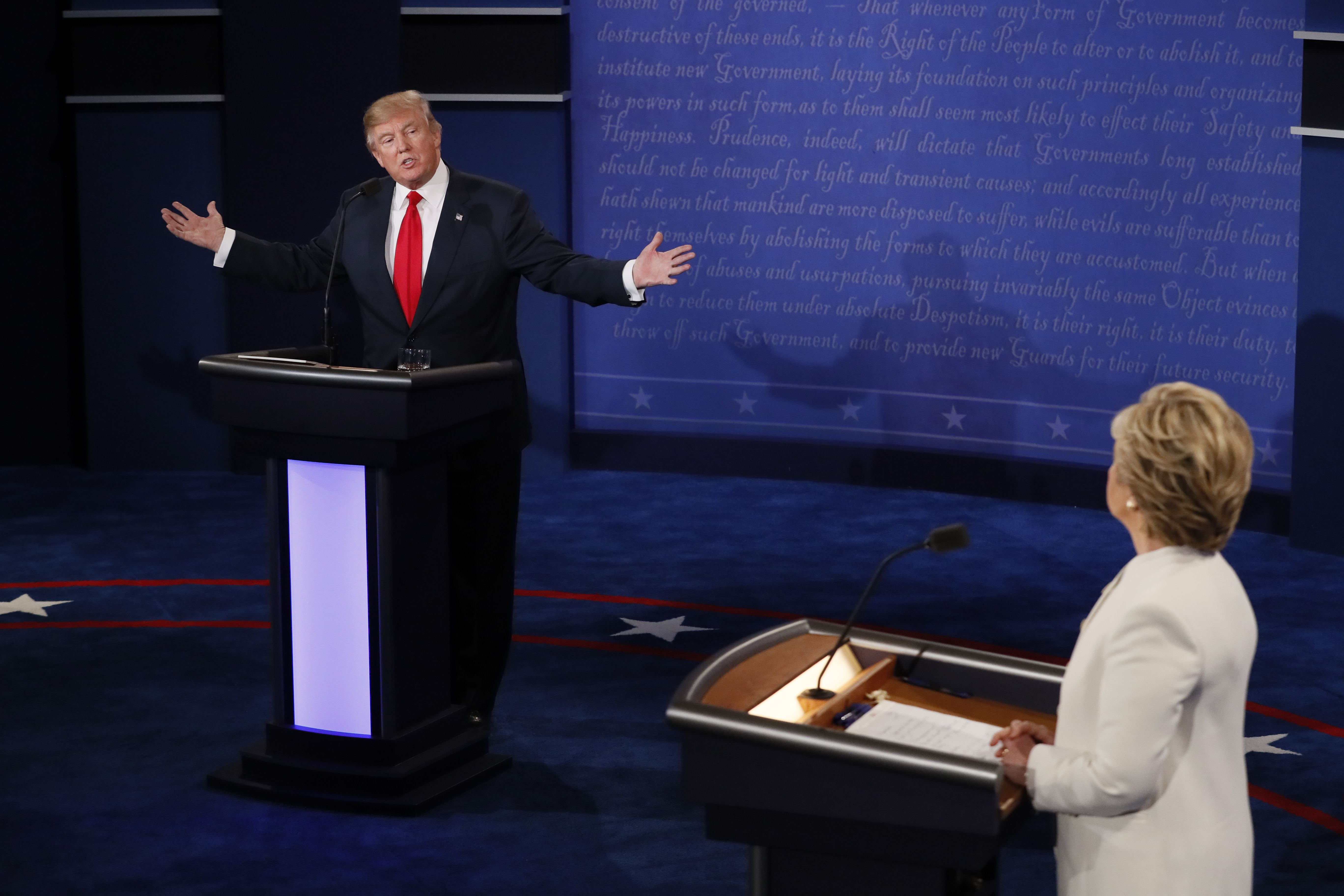 Republican presidential nominee Donald Trump speaks as Democratic presidential nominee Hillary Clinton (R) looks on during the final presidential debate at the Thomas & Mack Center on the campus of the University of Las Vegas in Las Vegas on Oct. 19, 2016.