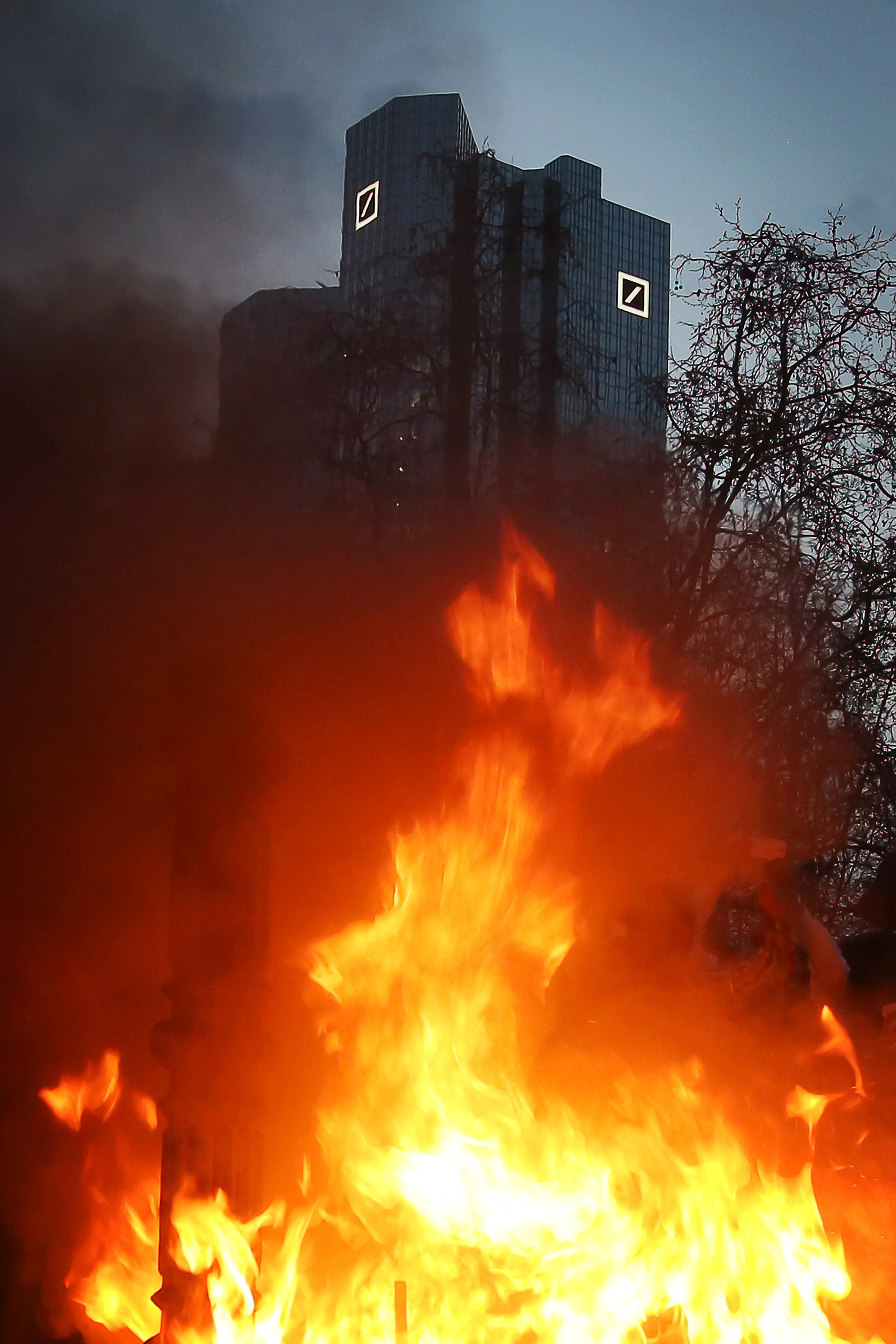 Protesters set fire to a pile of fake bills in front of the towers of the Deutsche Bank, while gathering for the closing rally on the Opernplatz (Opera Square) in Frankfurt, Germany, 18 March 2015. The new headquarters of the European Central Bank (ECB) in Frankfurt opened today amid protests. Photo by: Fredrik von Erichsen/picture-alliance/dpa/AP Images