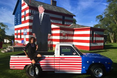 """Leslie Rossi sits outside of her """"Trump House"""" in Latrobe, Pennsylvania. She said thousands of people check out the house every week."""