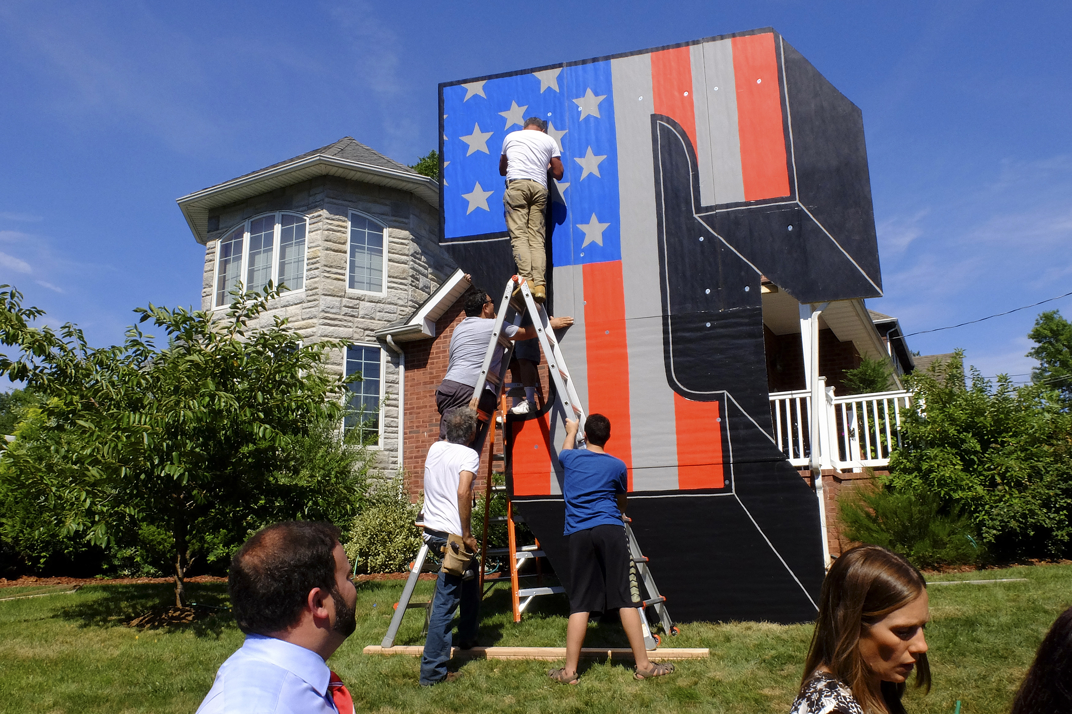 New York artist Scott LoBaido works on a 'Patriotic Lawn T' in support of Republican presidential nominee Donald Trump in the area of Castleton Corners on Staten Island, New York on Aug. 9, 2016.