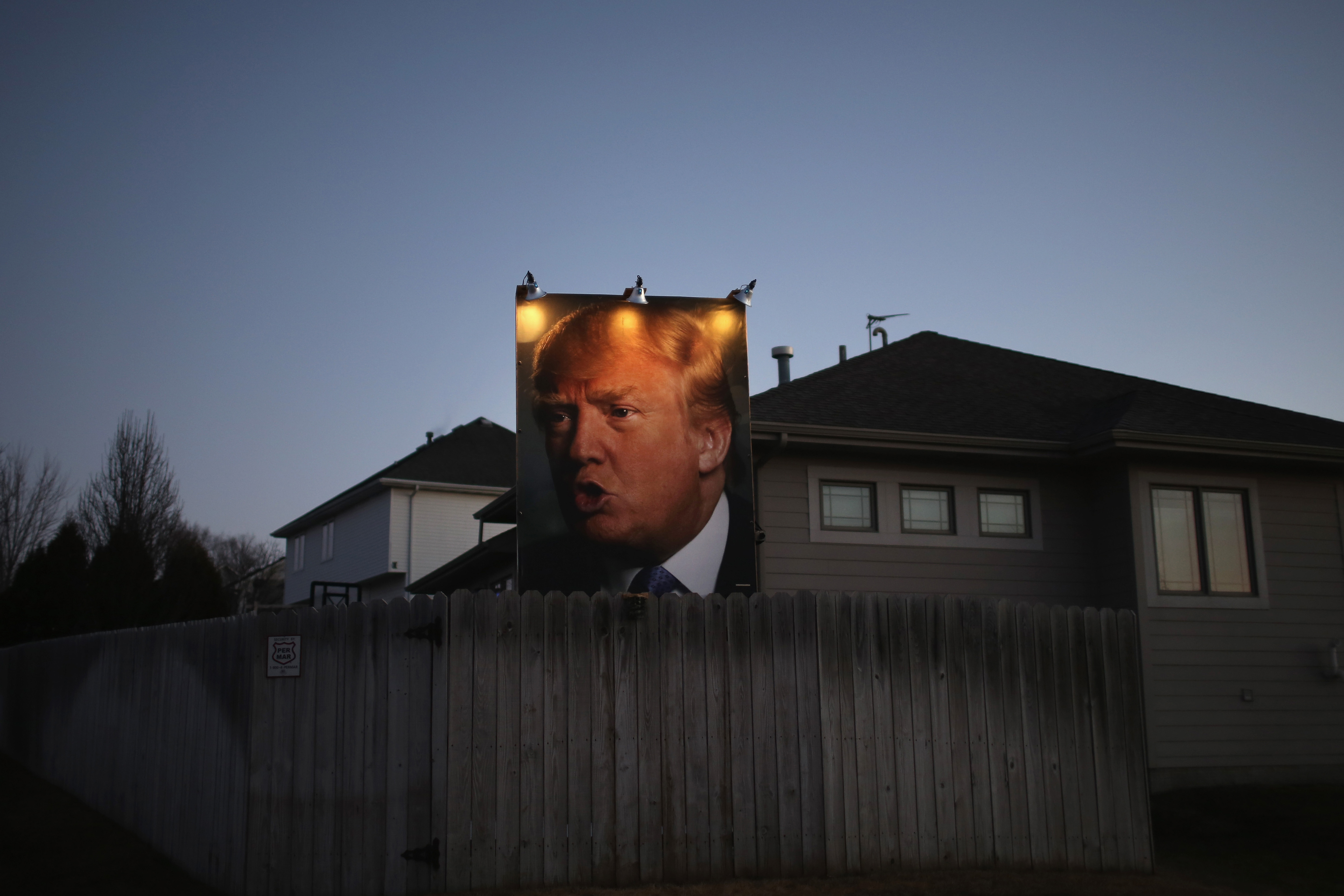 A giant poster of Republican presidential candidate Donald Trump is displayed by a supporter on Jan. 28, 2016 in Des Moines, Iowa.