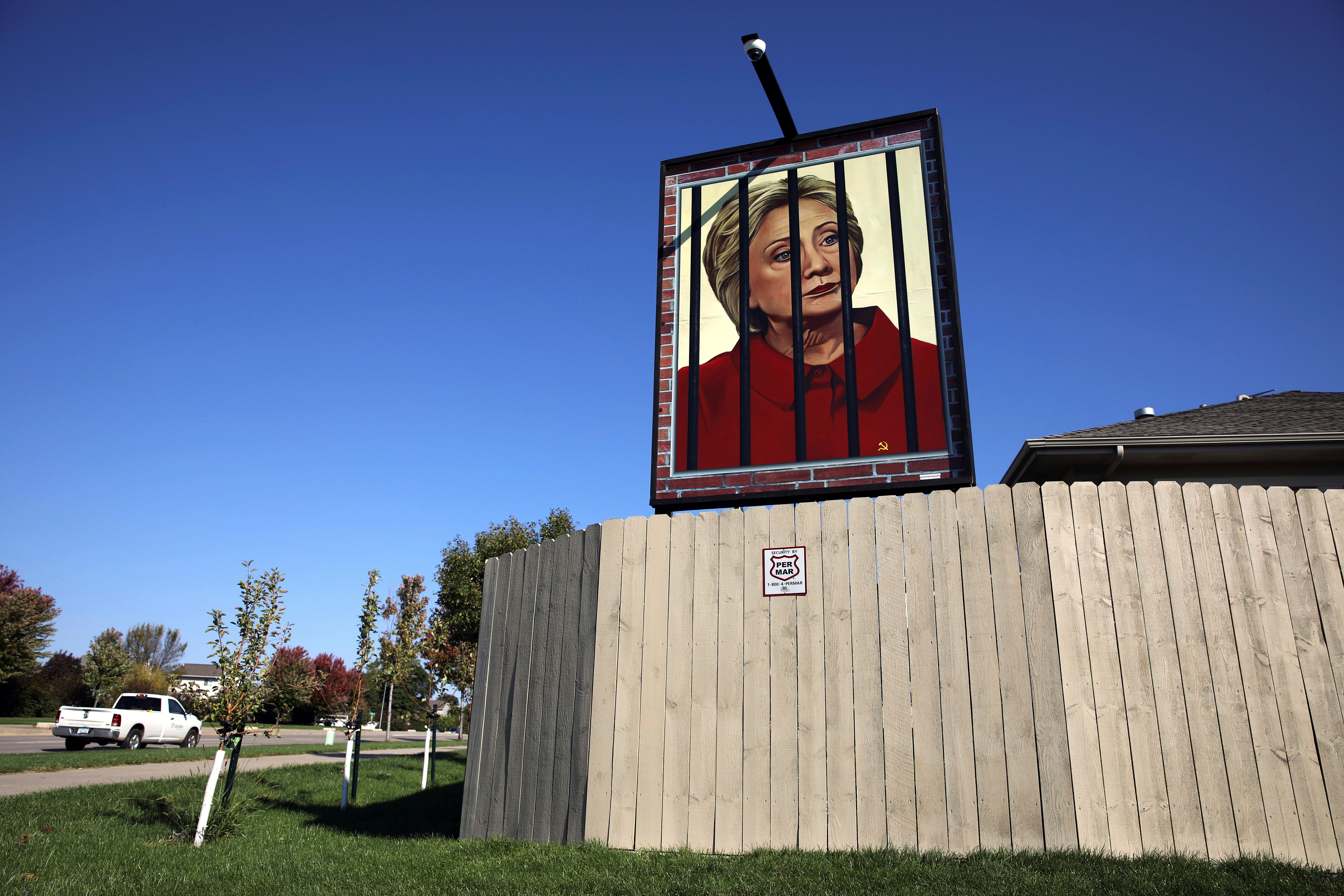A poster depicting U.S. Democratic presidential candidate Hillary Clinton behind bars hangs in the yard of George Davey in West Des Moines, Iowa, Oct. 11, 2016.