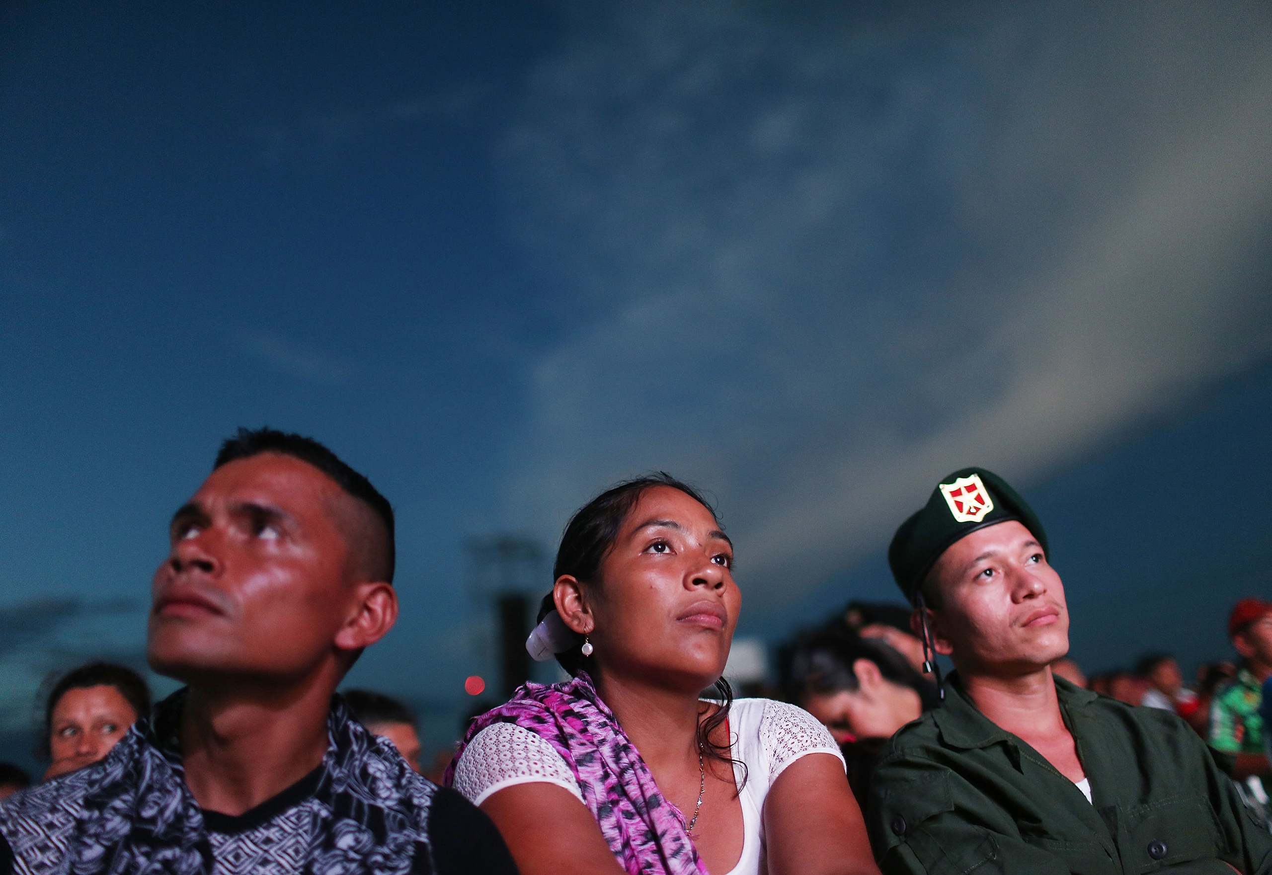 Revolutionary Armed Forces of Colombia (FARC) rebels watch a live broadcast of the peace agreement ceremony at a FARC encampment in the remote Yari plains near El Diamante, Colombia, on Sept. 26, 2016.