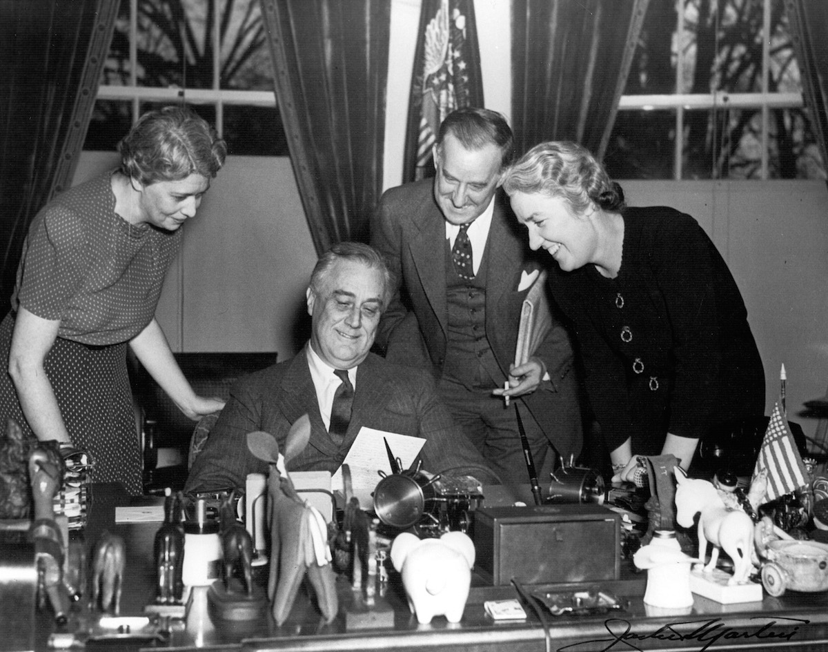 President Roosevelt at his desk in the White House with (left to right) Marguerite LeHand, Stephen Early, and Grace Tully, May 22, 1941.