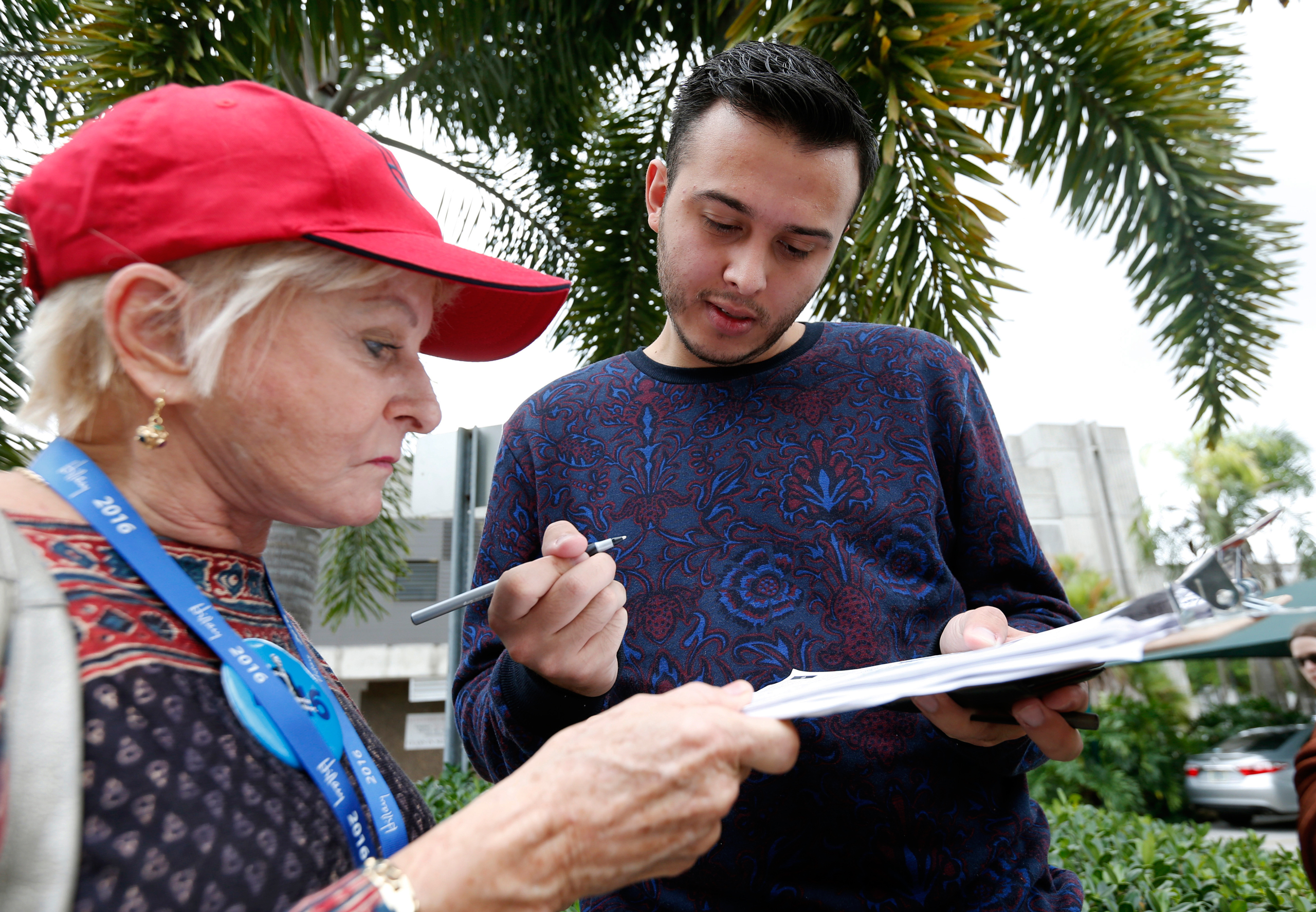 Volunteer Sandi Strickland, left, helps Roman Rodriguez fill out a new voter registration form in Miami on Oct. 11, 2016.