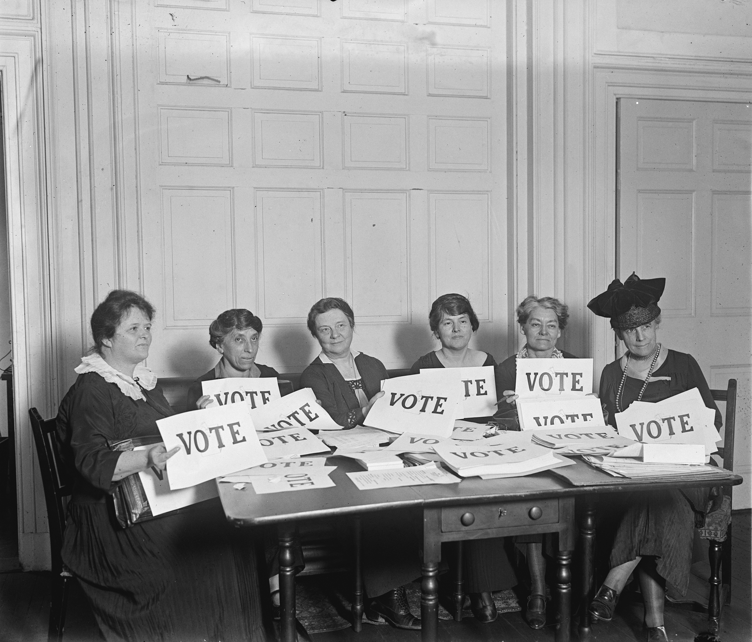 Members of the National League of Women Voters, seated around a table, holding signs that read VOTE, in Sep. 1924.