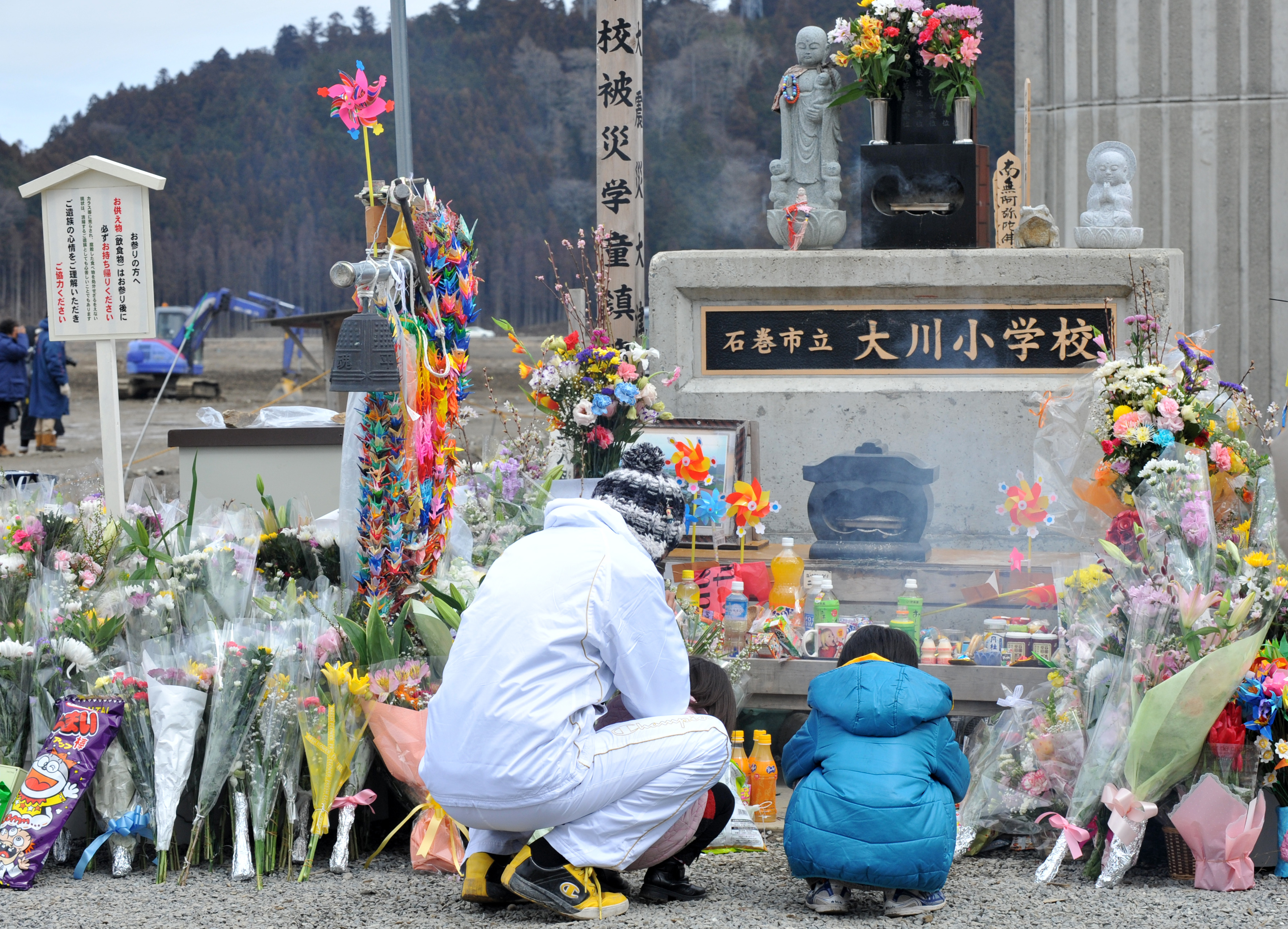 A family pray for 74 elementary-school students and 10 teachers who lost their lives in the March 11, 2011, earthquake and tsunami, at a memorial in front of the Okawa Elementary School during the first year anniversary of the disaster in Onagawa, Japan, on March 11, 2012