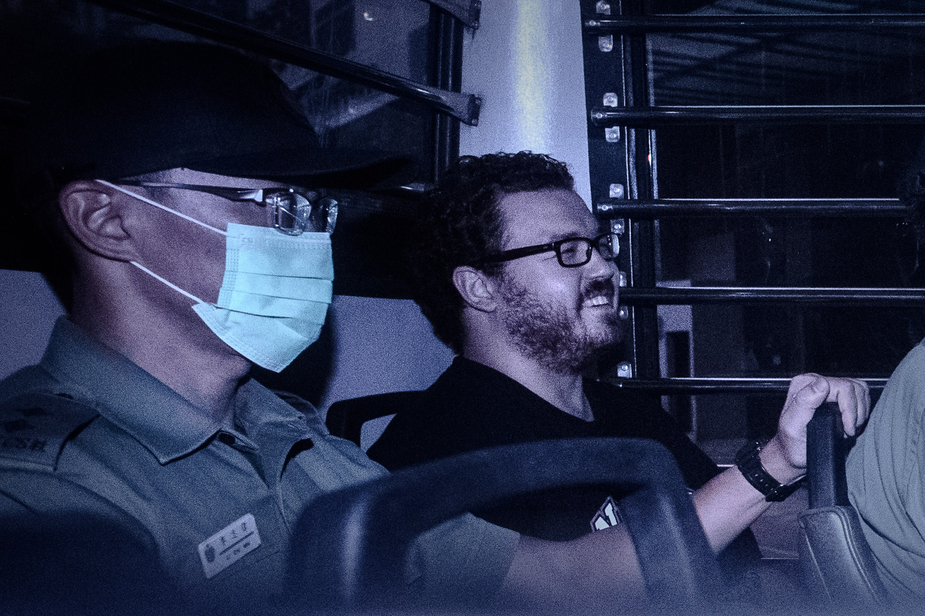 British banker Rurik Jutting, charged with the grisly murders of two women, smiles as he sits in a prison van leaving the Eastern Court in Hong Kong on Nov. 10, 2014