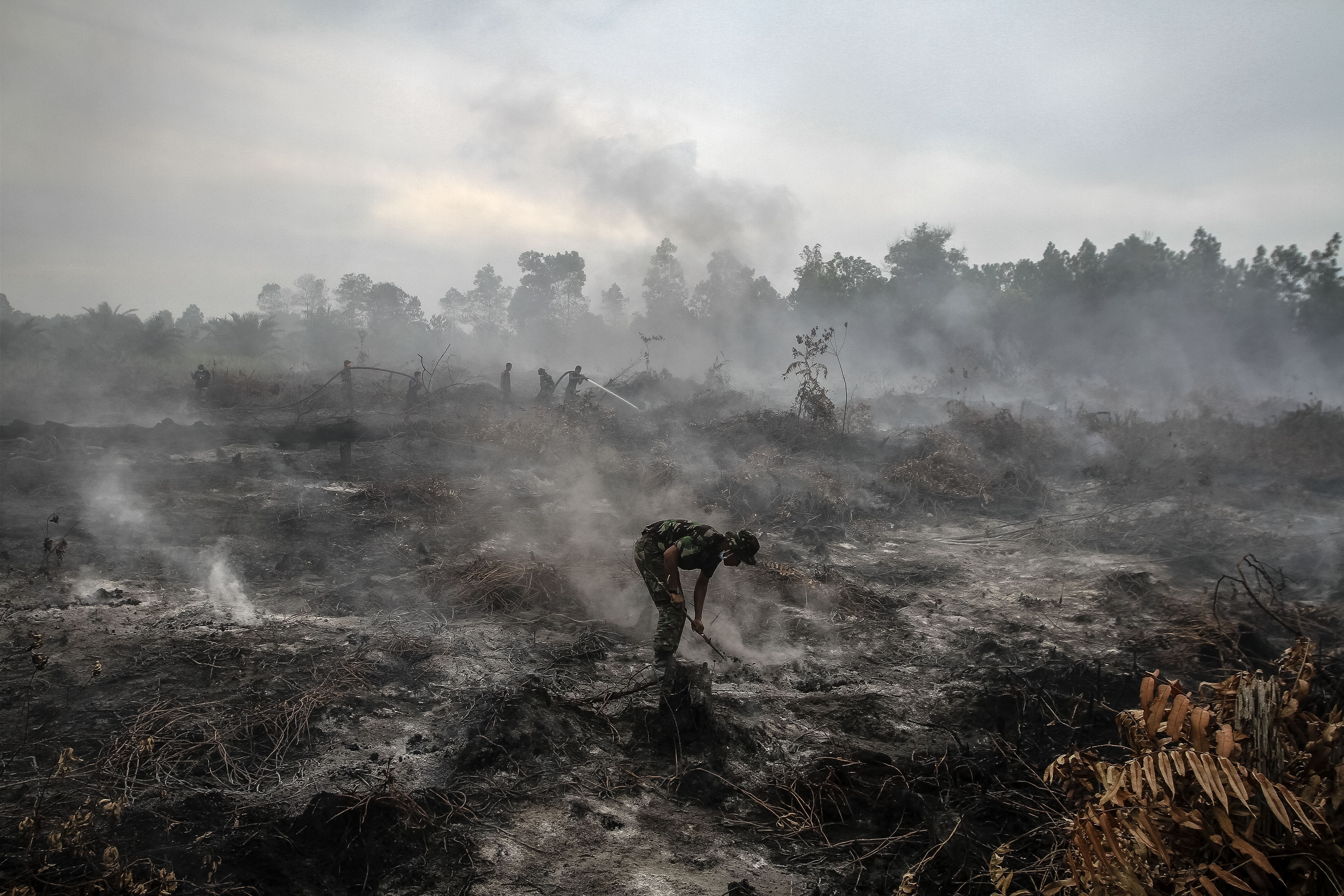 An Indonesian military personnel spray water on forest burned area at Rimbo Panjang Village, in Indonesia's Riau province, on Aug. 6, 2015