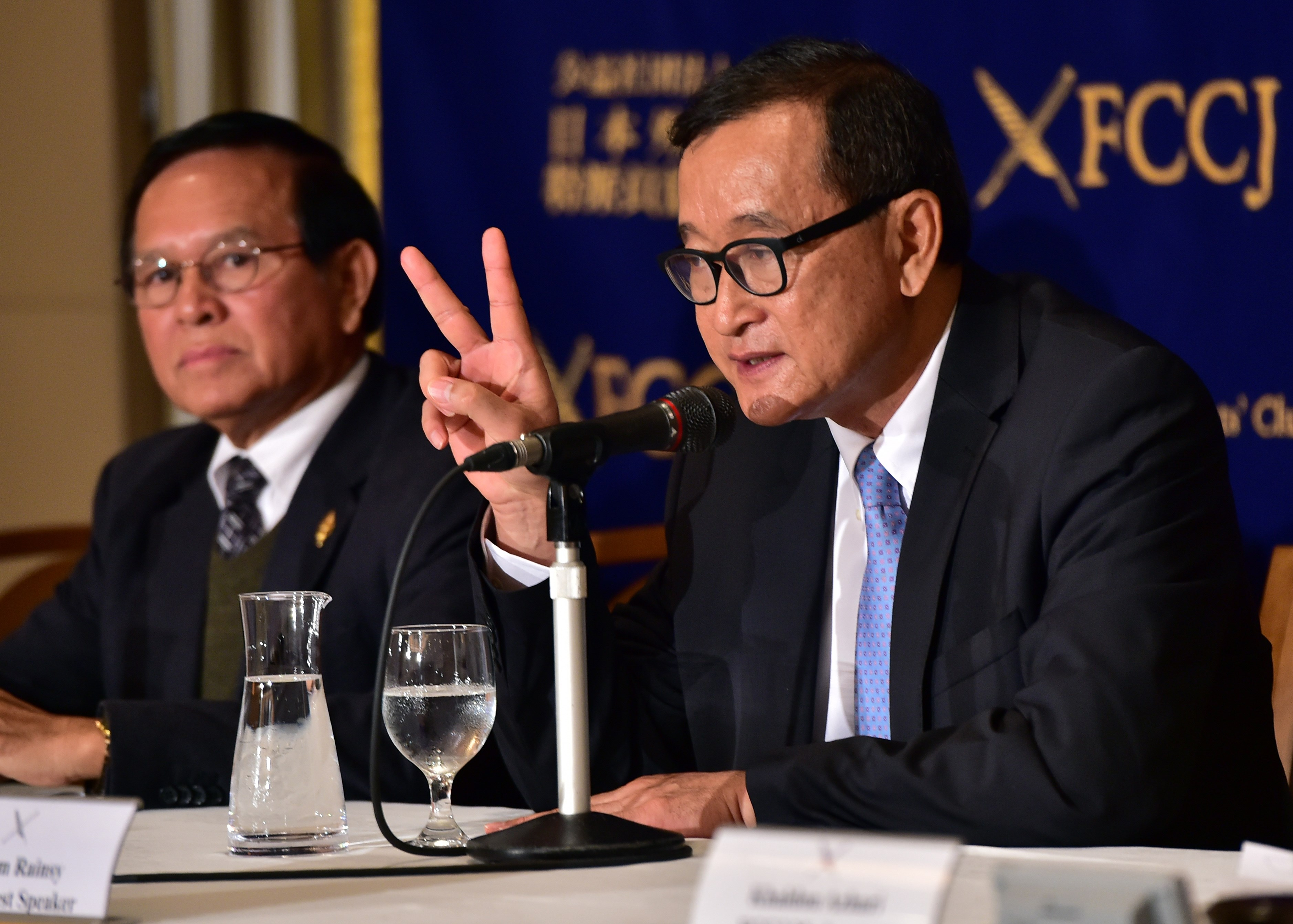 Cambodia's main opposition Cambodia National Rescue Party president Sam Rainsy, right, speaks to the press as deputy president Kem Sokha. left, looks on in Tokyo on Nov. 10, 2015