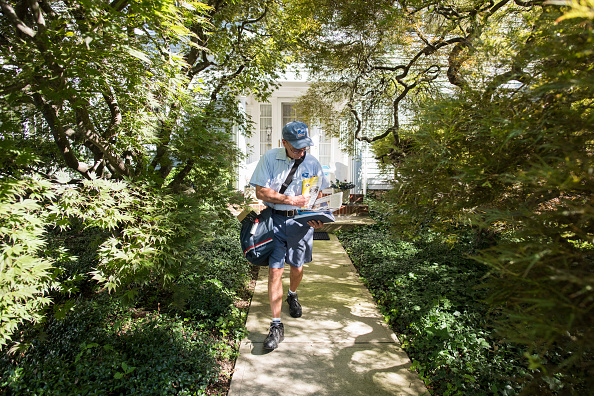 United States Postal Service (USPS) mailman Mike Micali makes deliveries in Flemington, New Jersey, U.S., on Thursday, Aug. 4, 2016.