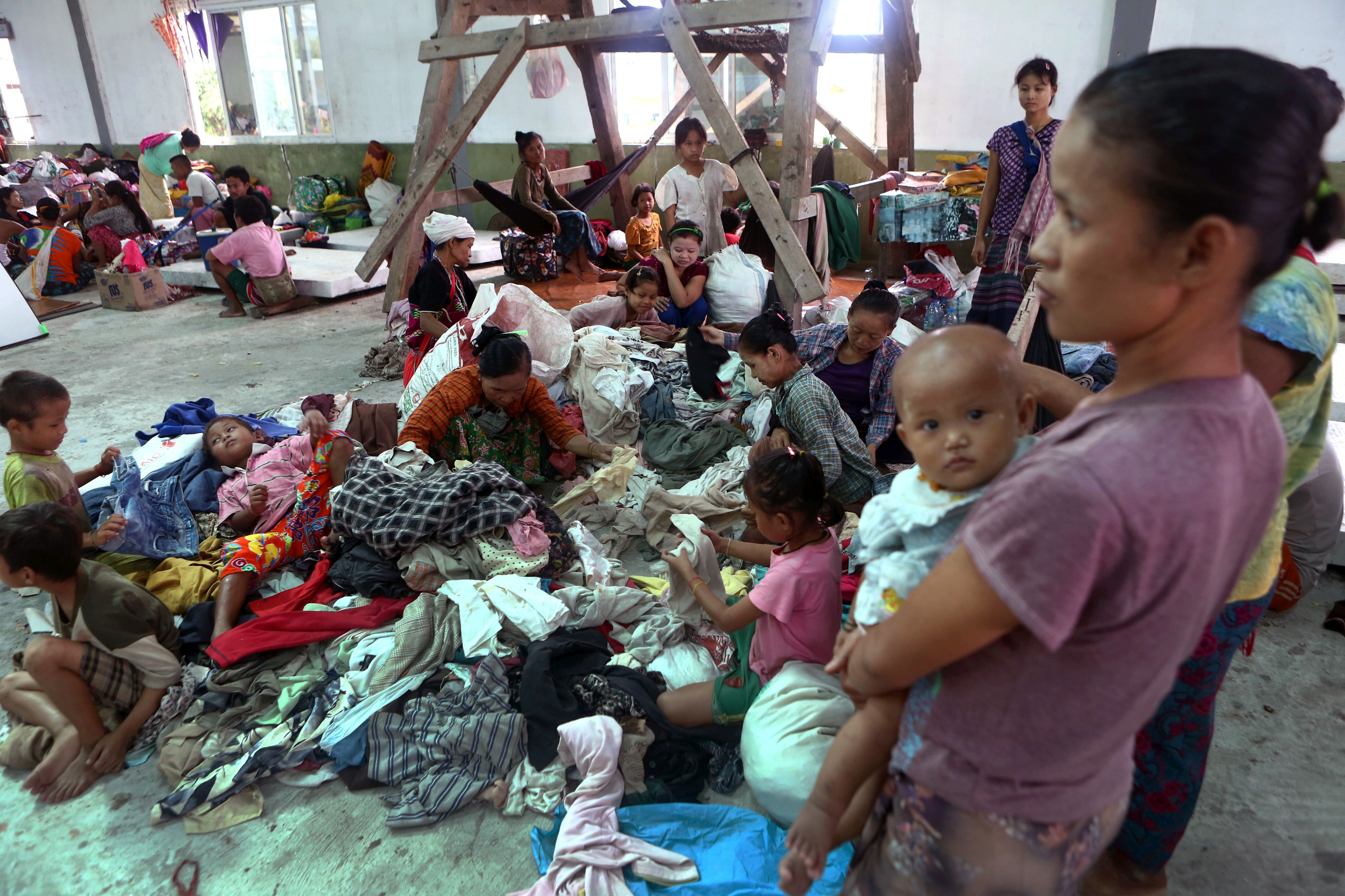 In this photo taken on September 21, 2016, residents who fled from conflict areas in Karen state take refuge at an evacuation center in a monastery in Myaing Gyi Ngu.                     At least eight people have been killed and thousands displaced by clashes in southeast Myanmar between government troops and an ethnic rebel splinter group belonging to the Democratic Karen Buddhist Army.