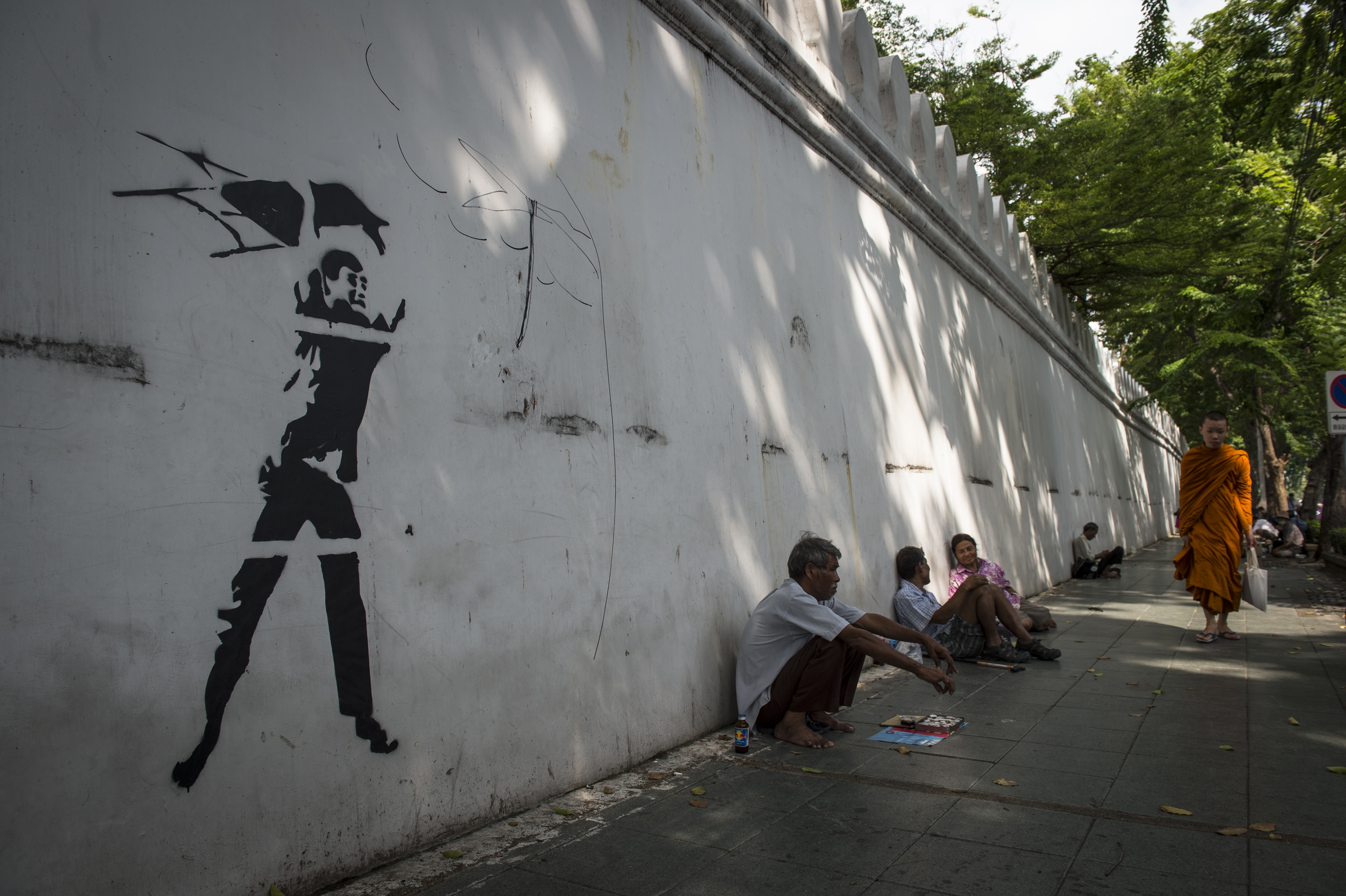 This photo taken on Sept. 30, 2016, shows graffiti depicting a violent ultra-royalist with a chair from the iconic photograph of the Oct. 6, 1976, student massacre by Associated Press photographer Neil Ulevich, on the outside wall of Thammasat University in Bangkok