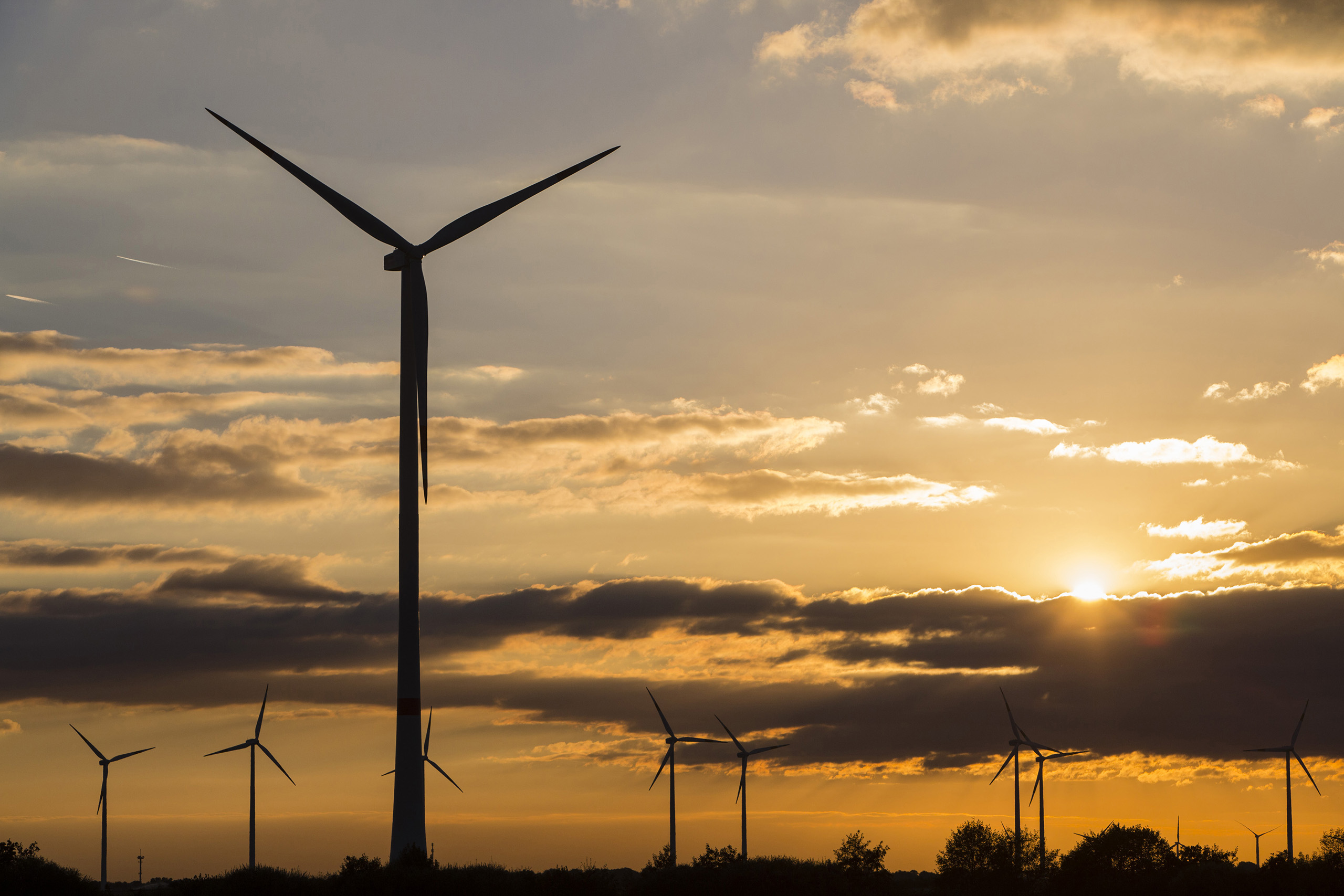 Wind turbines operate on the Innogy SE wind farm as the sunsets in Bedburg, Germany, on Oct. 4, 2016.
