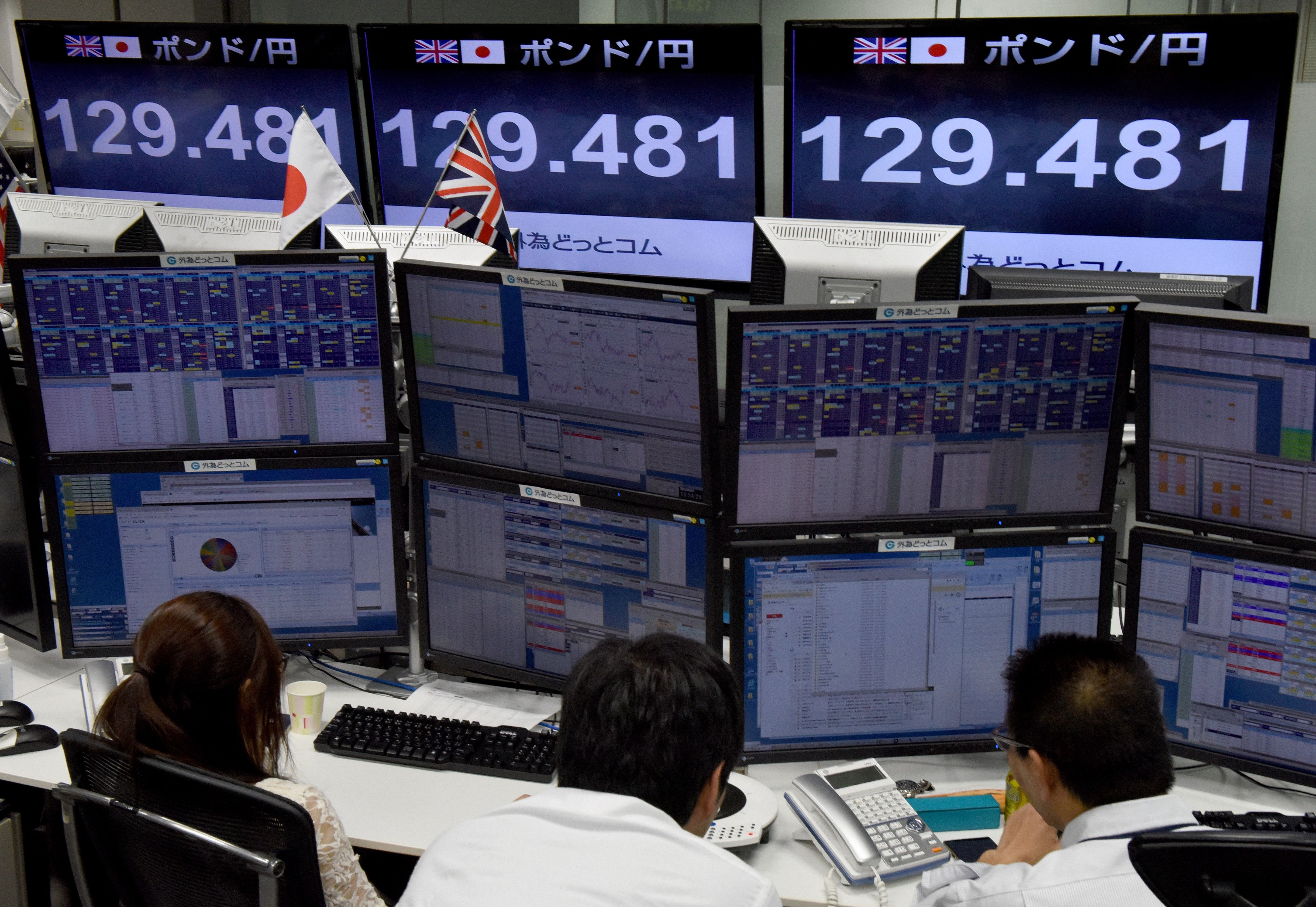 Traders ckeck computer screens showing the Japanese yen rate against the British pound at a brokerage in Tokyo on Oct. 7, 2016.