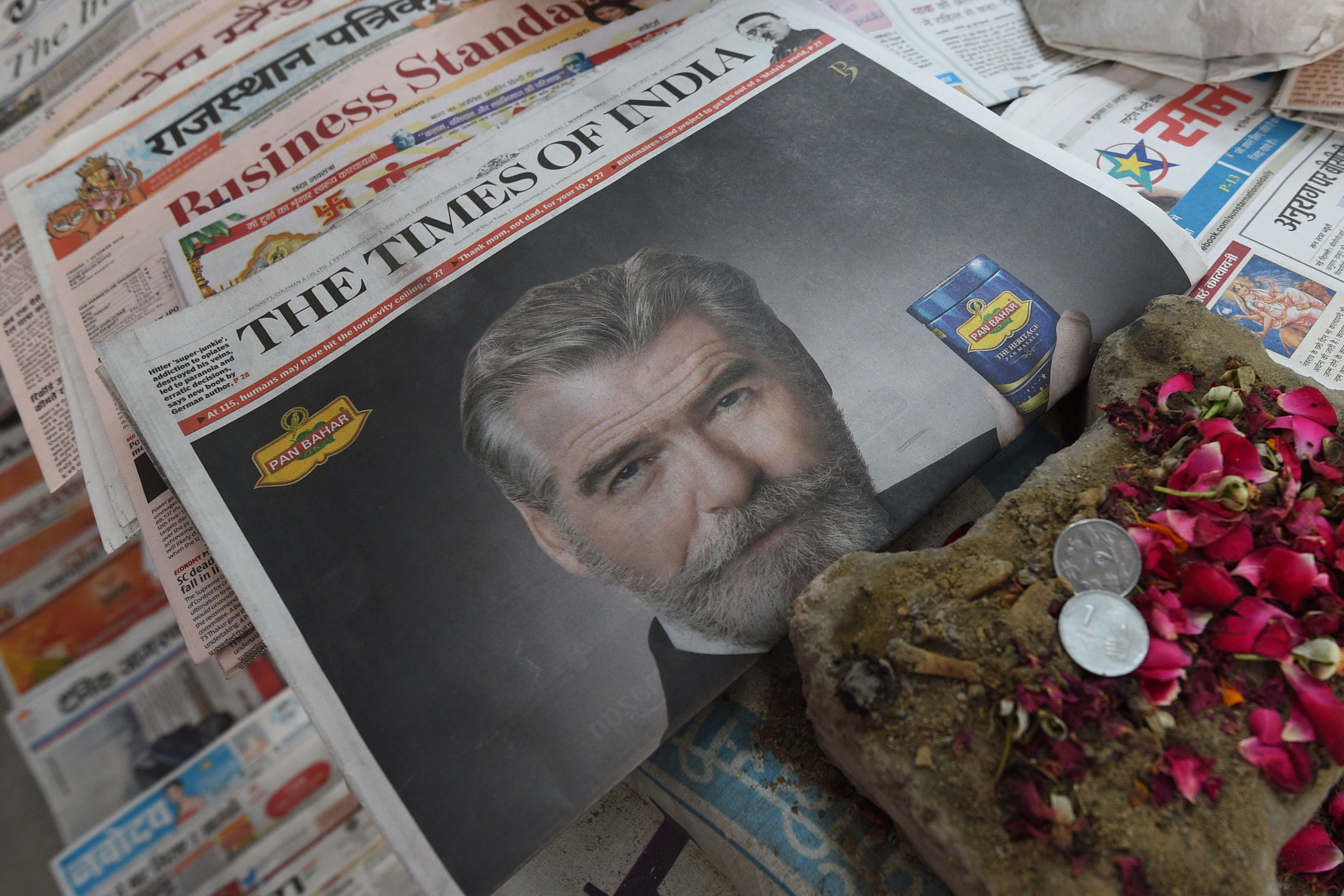 A newspaper with a front page advertisement of Pierce Brosnan endorsing an Indian mouth freshener, is seen on the streets of New Delhi on Oct. 7, 2016.