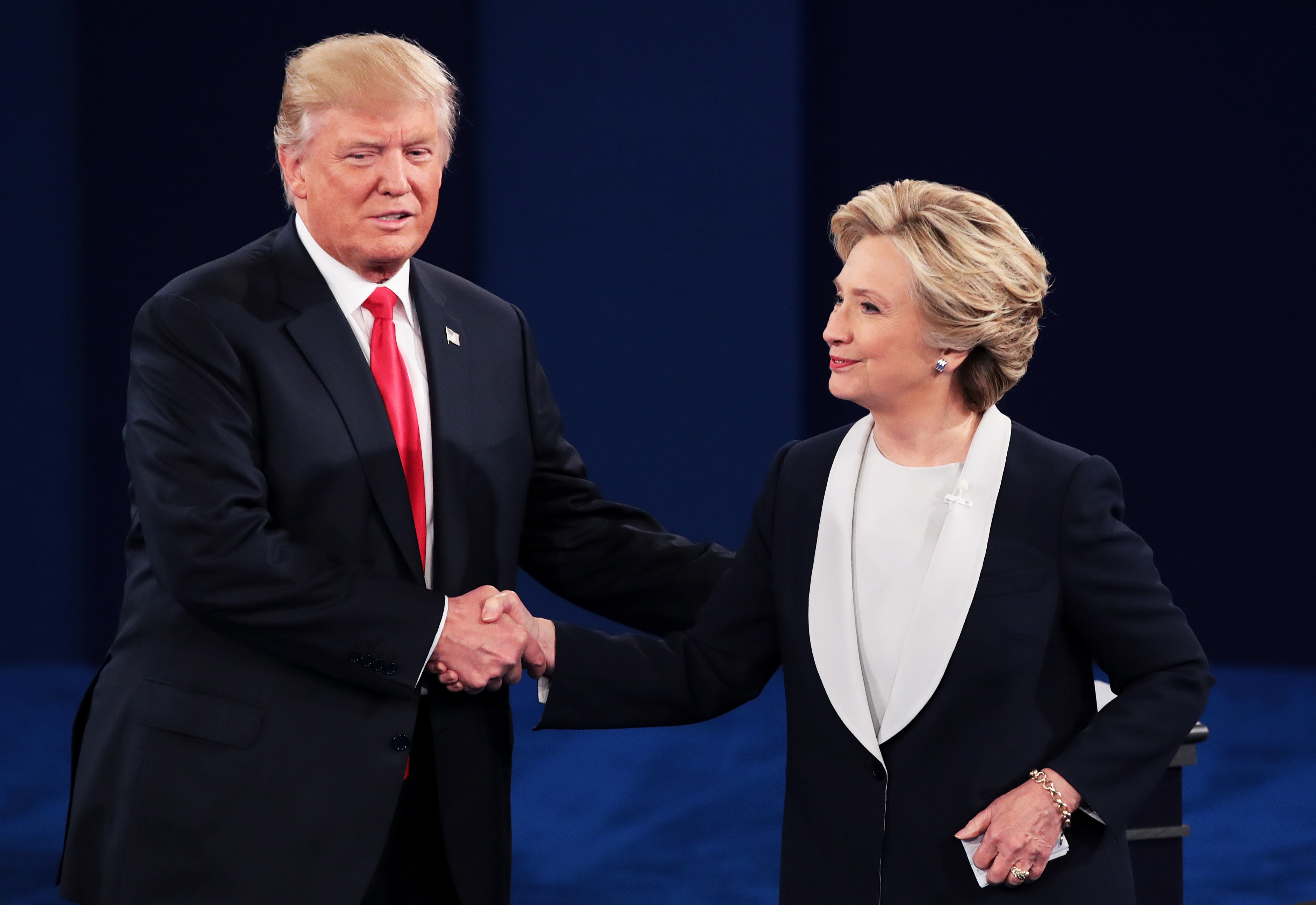 Republican presidential nominee Donald Trump (L) shakes hands with Democratic presidential nominee former Secretary of State Hillary Clinton during the town hall debate at Washington University on October 9, 2016 in St Louis, Missouri. This is the second of three presidential debates scheduled prior to the November 8th election.