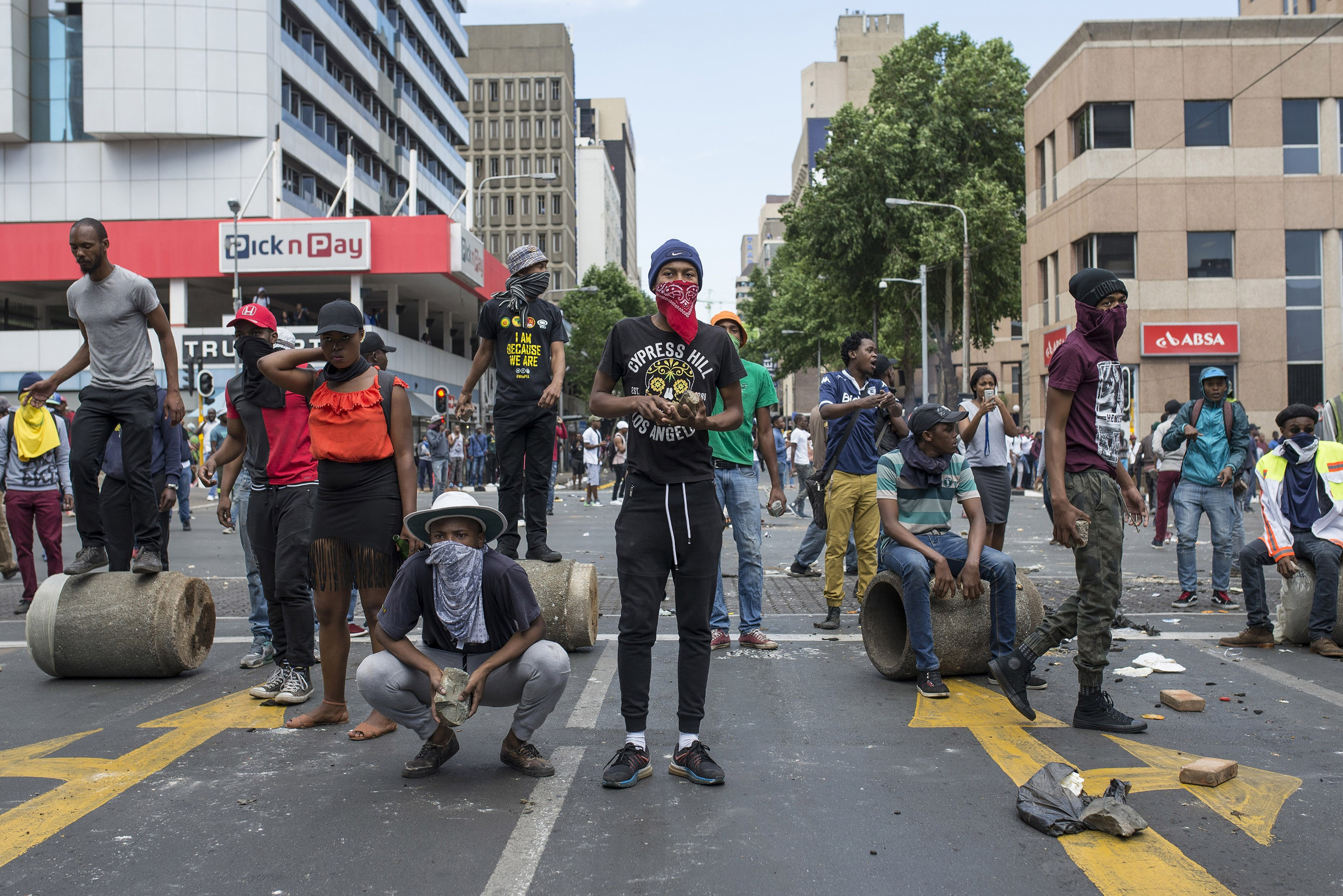 A group of students take cover as the clashes between students and riot police continues during a protest over government's plan of increasing university tuition fees on Oct. 10, 2016 in Witwatersrand University, Johannesburg.