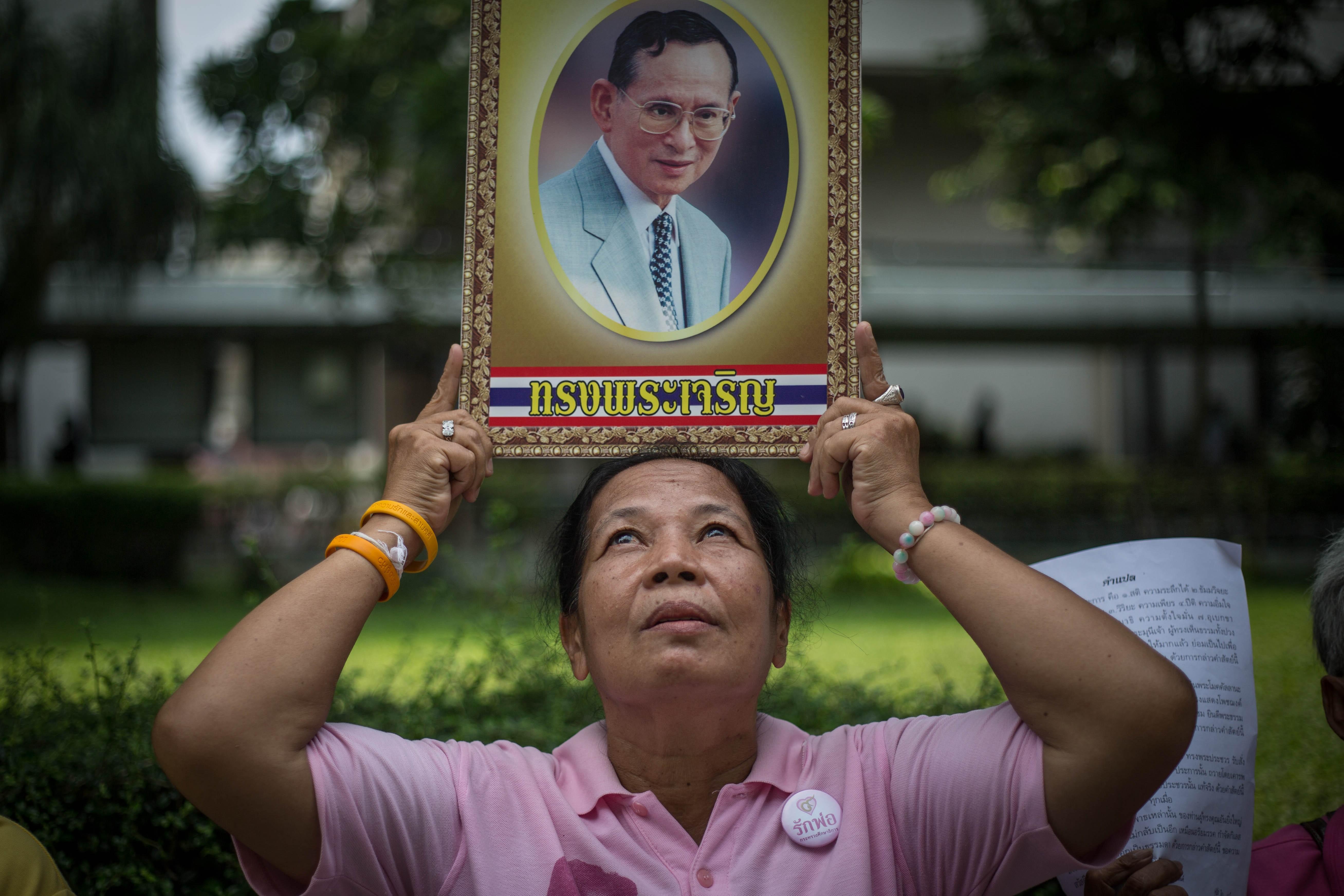 A Thai Royalist holds a portrait of Thailand's King Bhumibol Adulyadej at Siriraj Hospital as his health has deteriorated on Oct. 11, 2016.