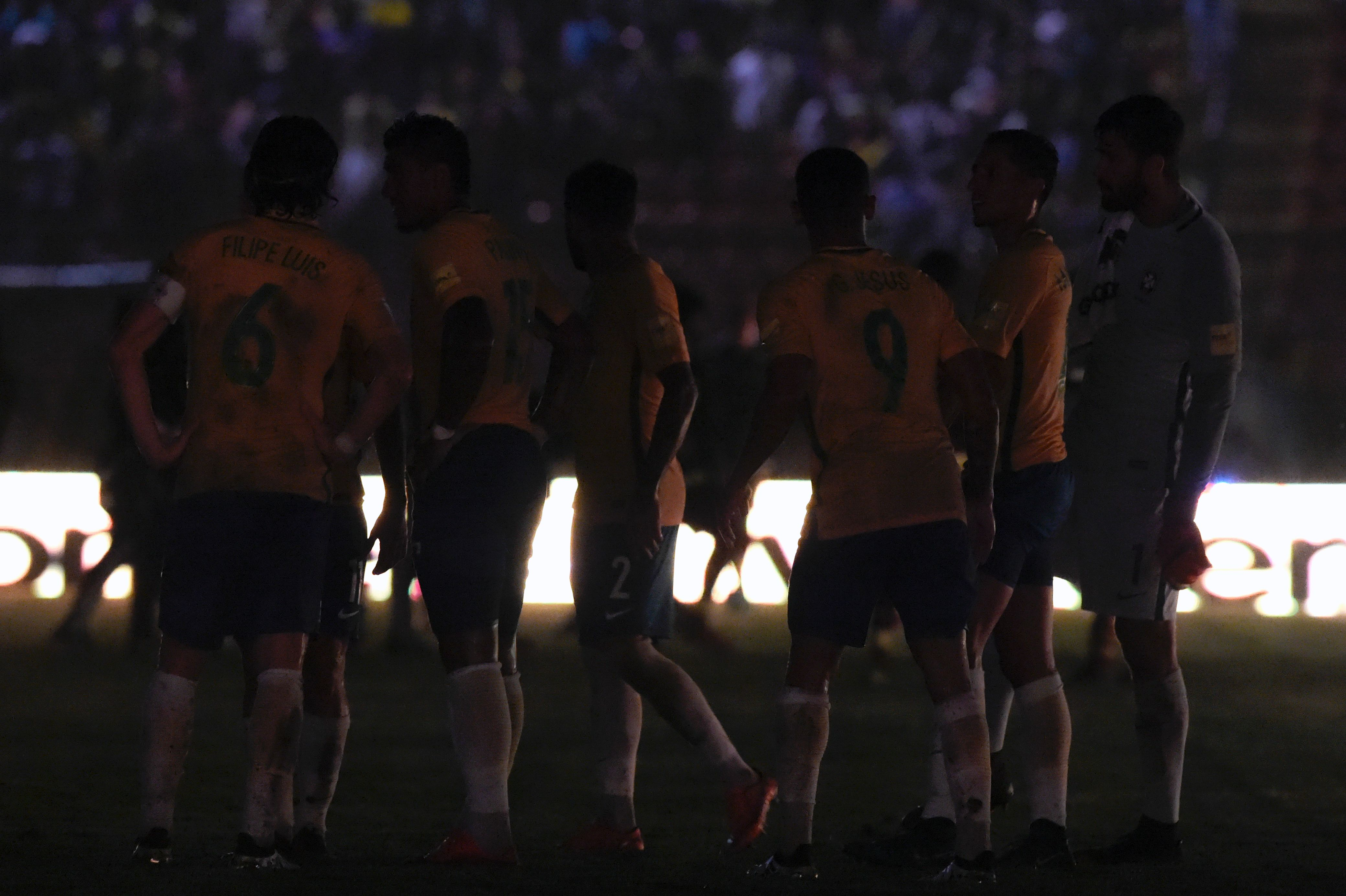 Brazilian players are seen on the field as a blackout occured during the Russia 2018 FIFA World Cup qualifier football match against Venezuela, in Merida, Venezuela, on October 11, 2016.