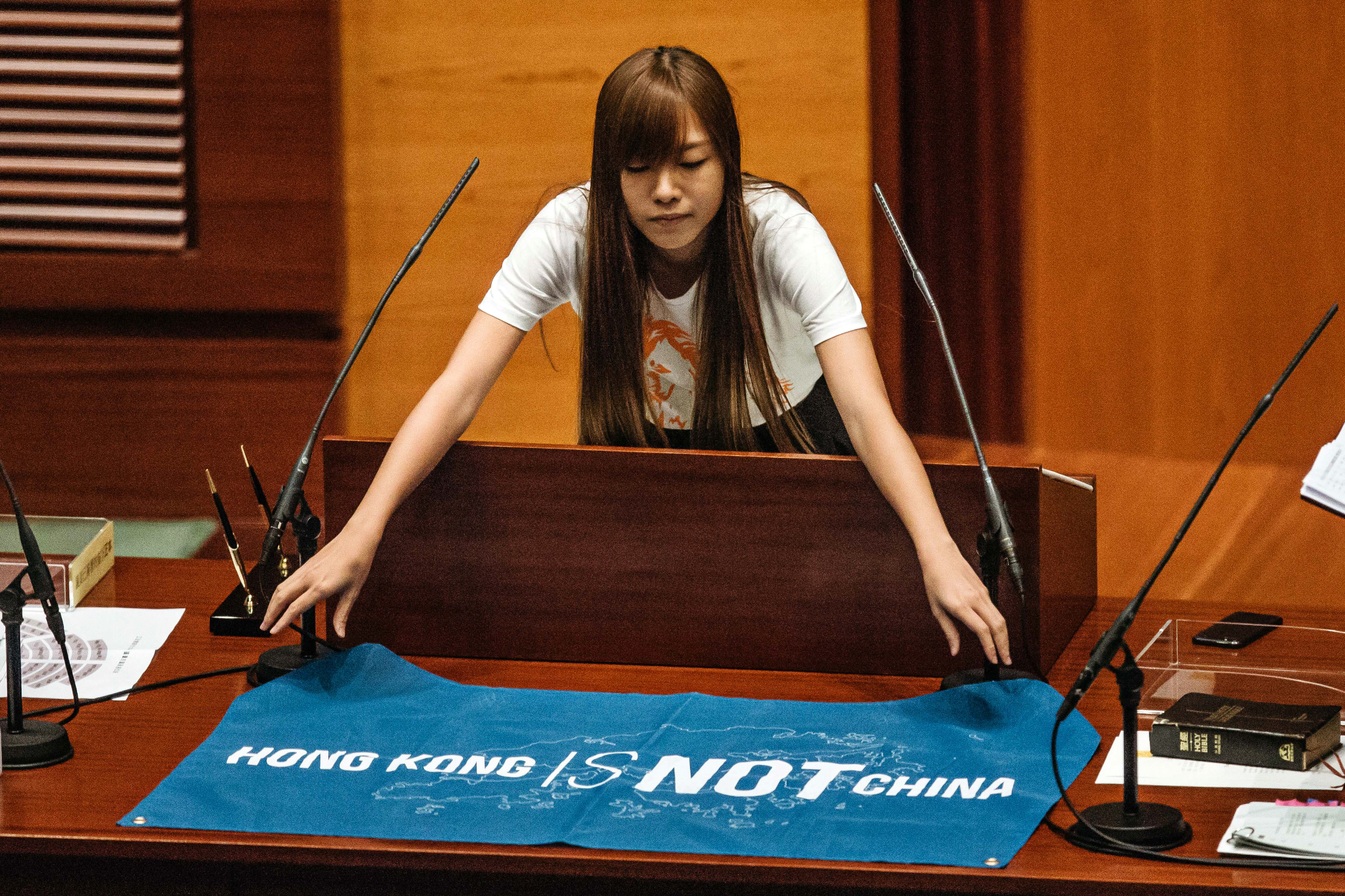 Yau Wai-ching, an incoming lawmaker and member of Youngspiration, unfurls a banner that reads  Hong Kong Is Not China  during an oath-taking ceremony in the chamber of the Legislative Council in Hong Kong on Oct. 12, 2016