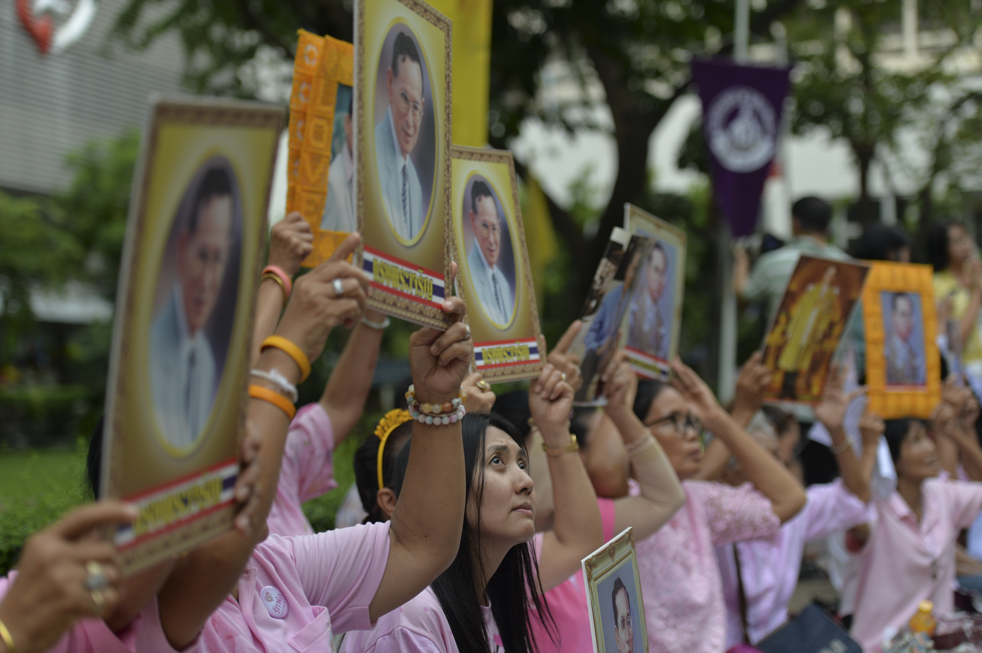 Thai women hold portraits of Thai King Bhumibol Adulyadej as they pray for his health at Siriraj Hospital, where the king is being treated, in Bangkok on Oct. 12, 2016.