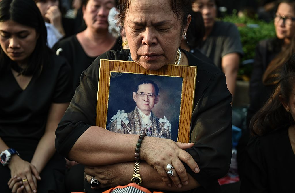 A mourner clutches a picture of Thai King Bhumibol Adulyadej after the hearse carrying the body of the late monarch passes the Grand Palace in Bangkok on October 14, 2016.                   Bhumibol, the world's longest-reigning monarch, passed away aged 88 on October 13, 2016 after years of ill health, removing a stabilising father figure from a country where political tensions remain two years after a military coup. / AFP / LILLIAN SUWANRUMPHA        (Photo credit should read LILLIAN SUWANRUMPHA/AFP/Getty Images)