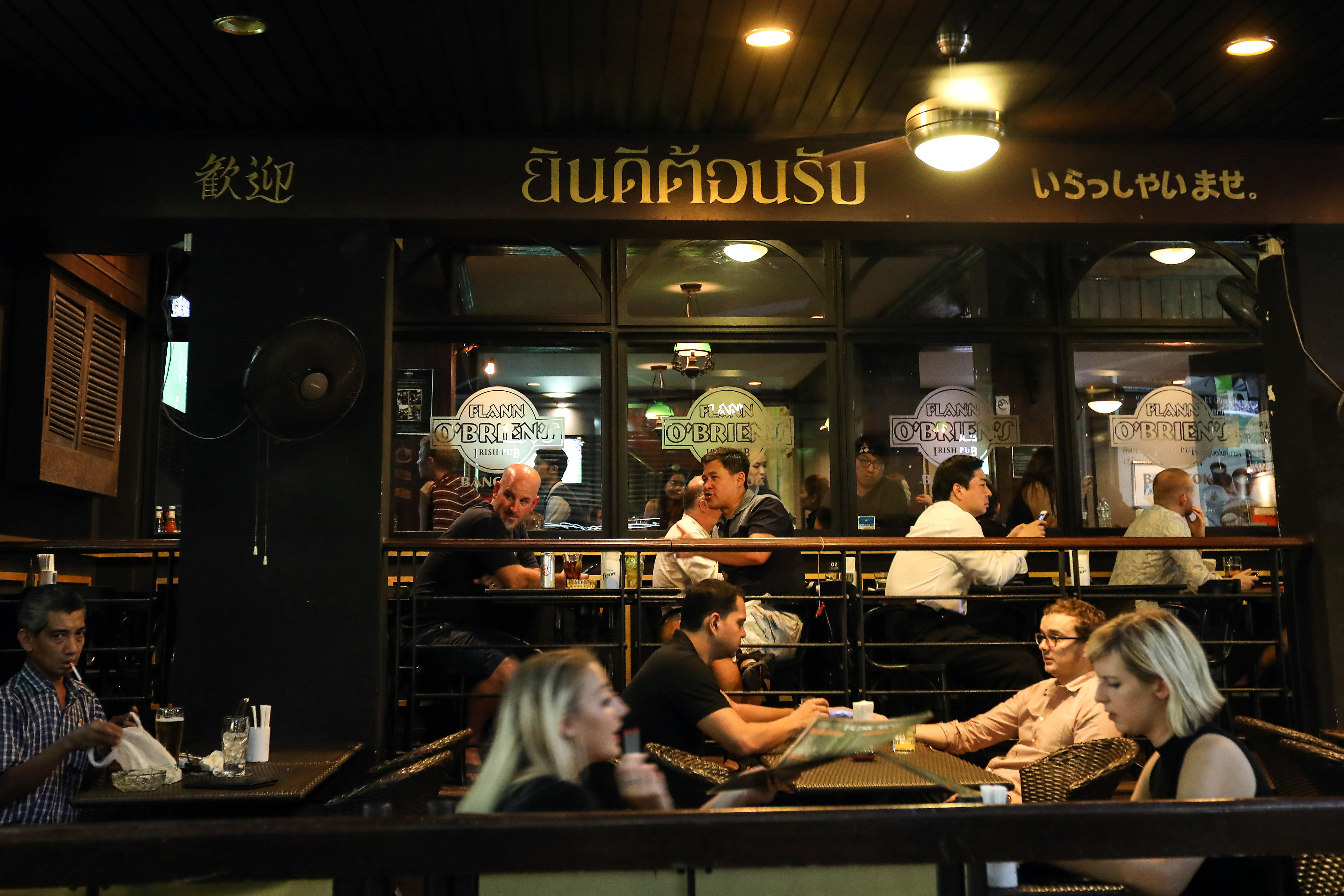 Customers sit and drink at a bar at night in the Silom area of Bangkok on Oct. 15, 2016
