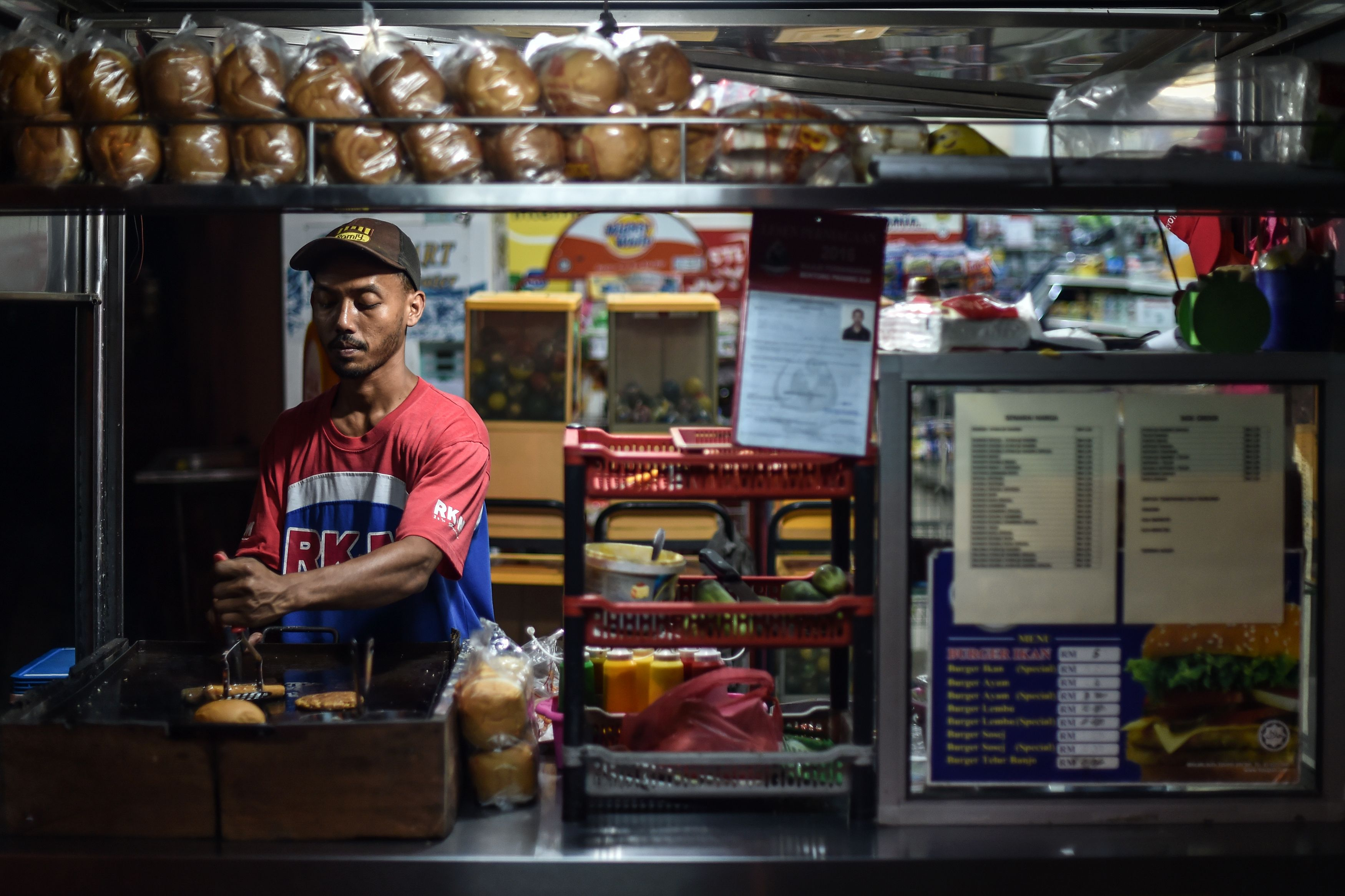 An employee cooks burgers and hotdogs at a roadside stall in Karak, outside Kuala Lumpur, on Oct. 18, 2016