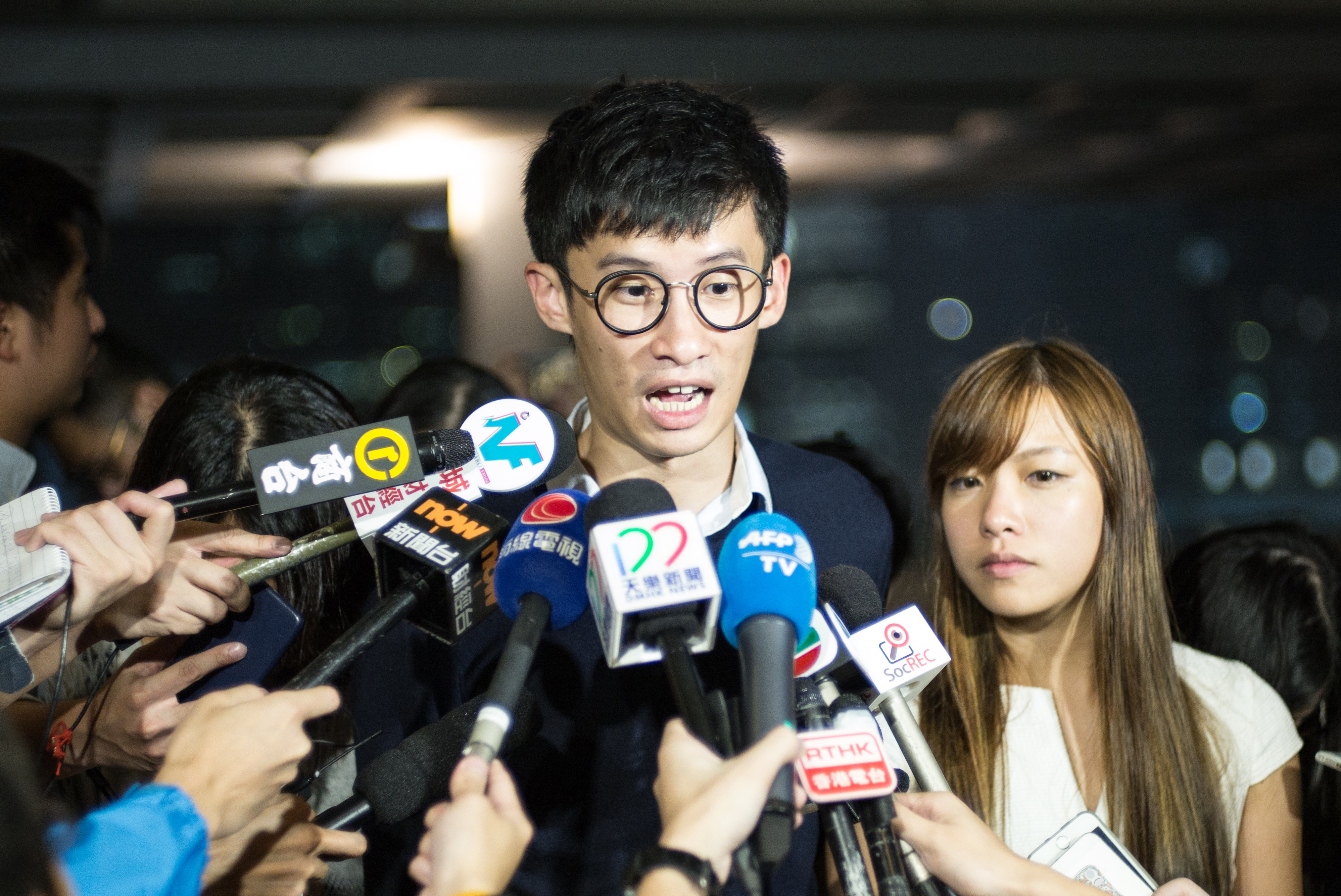 Newly-elected pro-independence Hong Kong lawmakers Sixtus  Baggio  Leung (C) and Yau Wai-ching (R) speak to the press outside the territory's High Court, Oct. 18, 2016.
