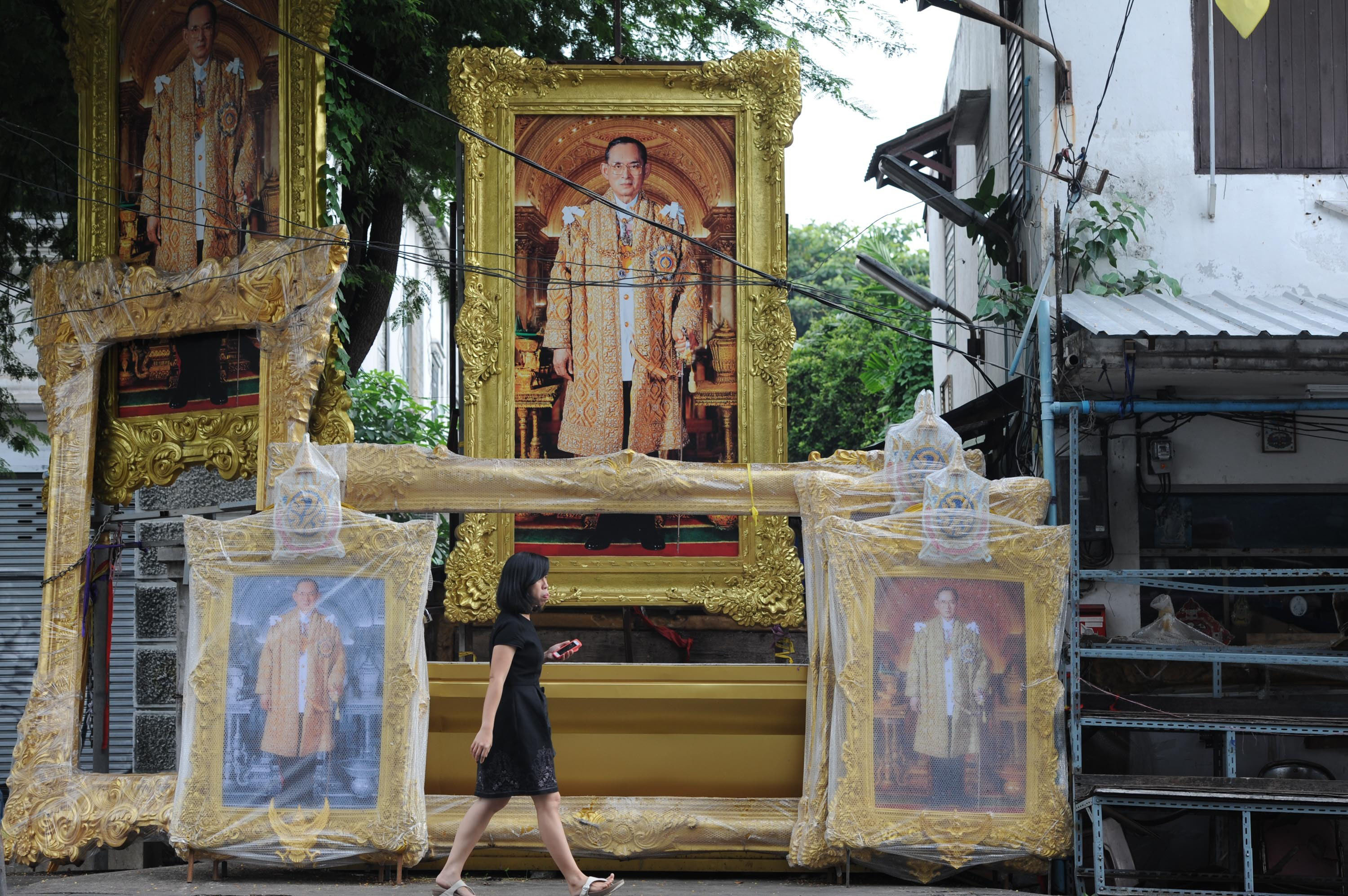 A woman walks past portraits of the late Thai King Bhumibol Adulyadej in downtown Bangkok, Thailand, Oct. 18, 2016