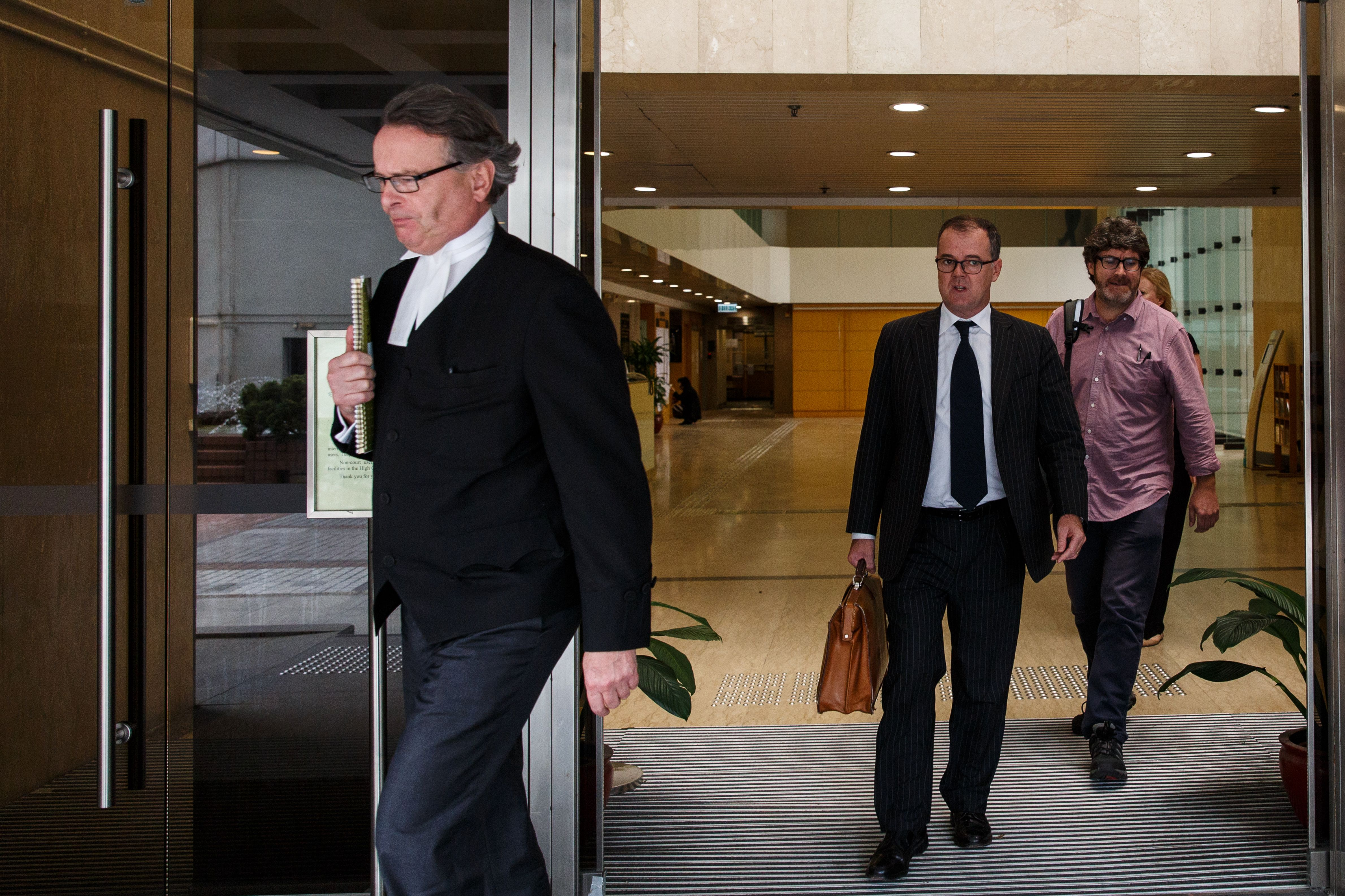 Barrister Tim Owen, left, and solicitor Michael Vidler, center, defending former British banker Rurik Jutting (not seen), 31, who is accused of the murders of two Indonesian women, leave the High Court during a break for lunch in Hong Kong on Oct. 24, 2016, on the first day of what is the city's biggest murder case for years