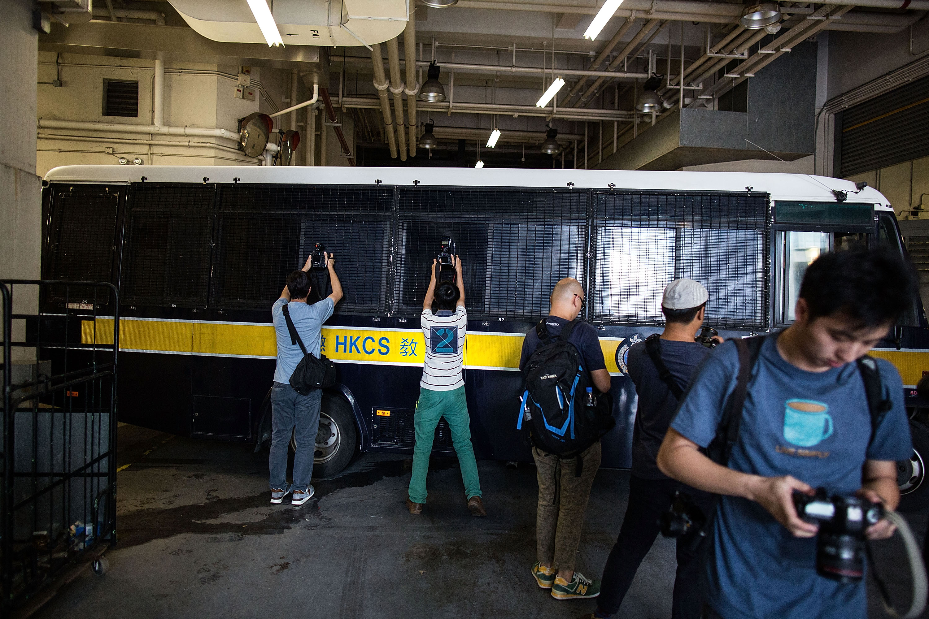 Journalists take photographs when a prison vehicle escorting Rurik Jutting leaves the High Court on Oct. 24, 2016, in Hong Kong