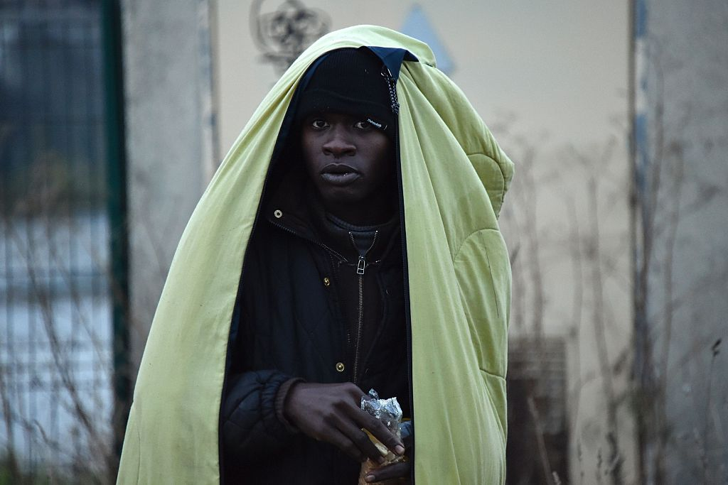 A migrant wrapped in a blanket eats near the  Jungle  migrant camp in Calais, France, on Oct. 27, 2016.