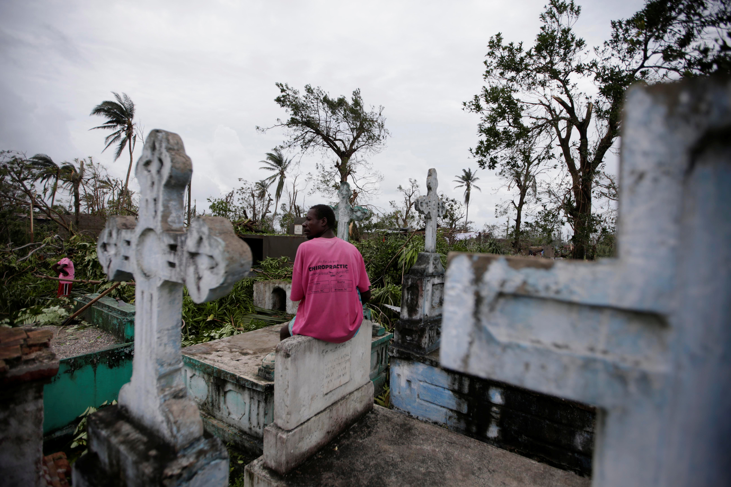 A man sits on a tombstone as he watches other clearing trees after Hurricane Matthew in Les Cayes, Haiti, on Oct. 6, 2016.