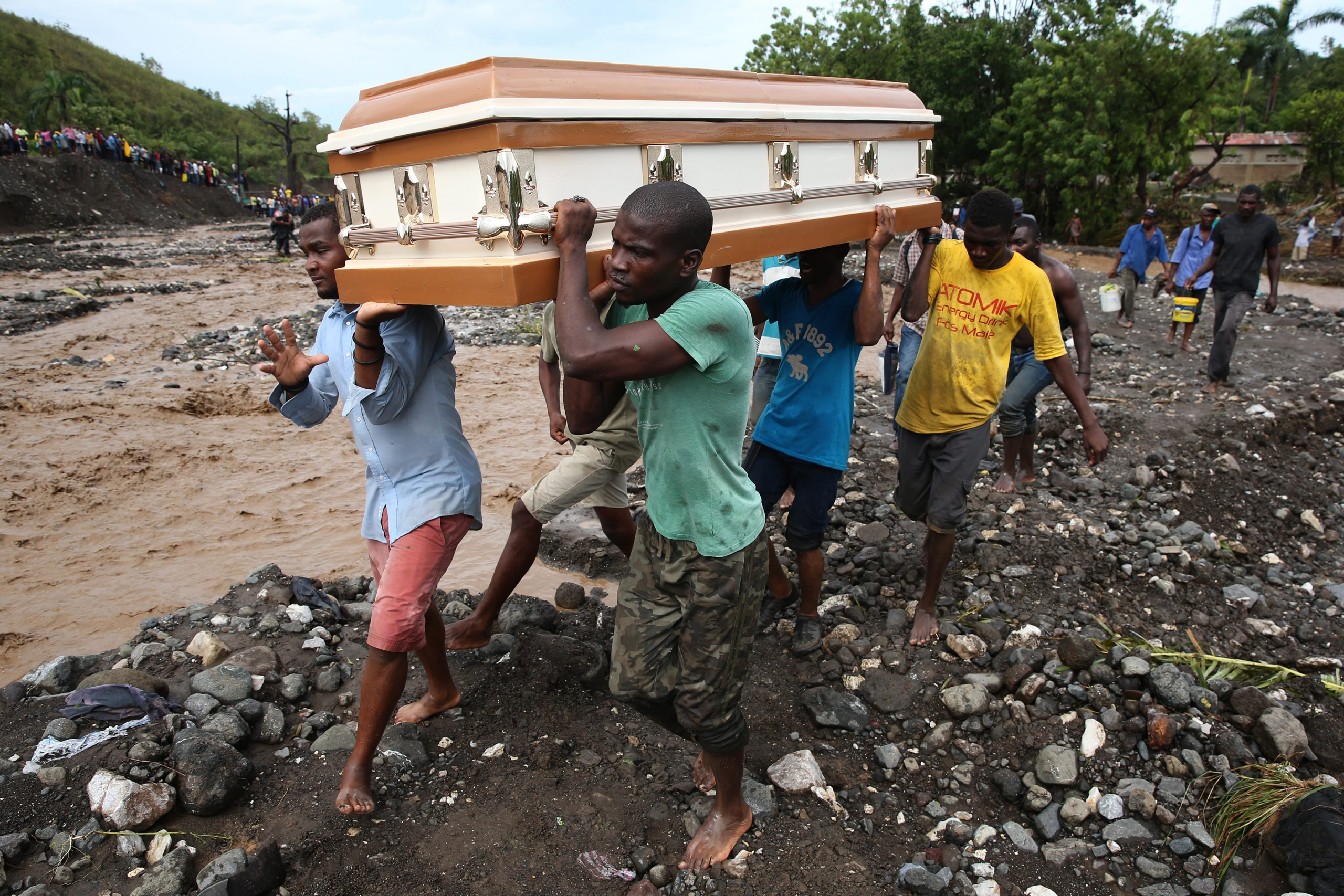 A group of people carry a coffin and try to cross the river La Digue, after the collapse of the only bridge that connects to the south after the passing of hurricane Matthew in the country, in Petit Goave, Haiti, on Oct. 5, 2016.